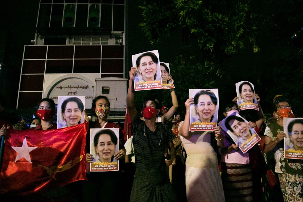 Supporters of the National League for Democracy (NLD) party hold portraits of Aung San Suu Kyi as they celebrate in front of the party's headquarters in Yangon on Nov. 9, 2020, as NLD officials said they were confident of a landslide victory in the weekend's election.