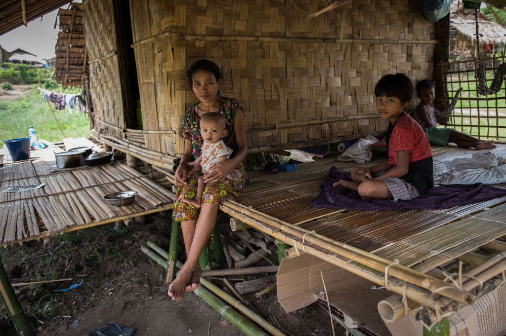 A family displaced by armed conflict between the Myanmar military and the Arakan Army sits at a temporary shelter in Hlegu Township on the outskirts of Yangon on June 25, 2020.