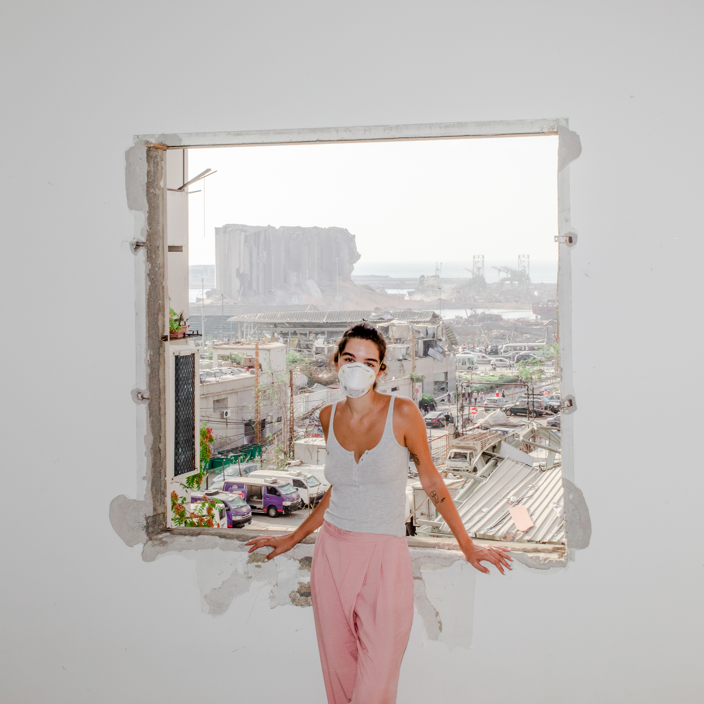 Nour Saliba stands in her apartment in the Mar Mikhael area of Beirut on Aug. 6, two days after the deadly explosion at the city's port, seen through her blown-out window.  After the Explosion,  Aug. 31 issue.