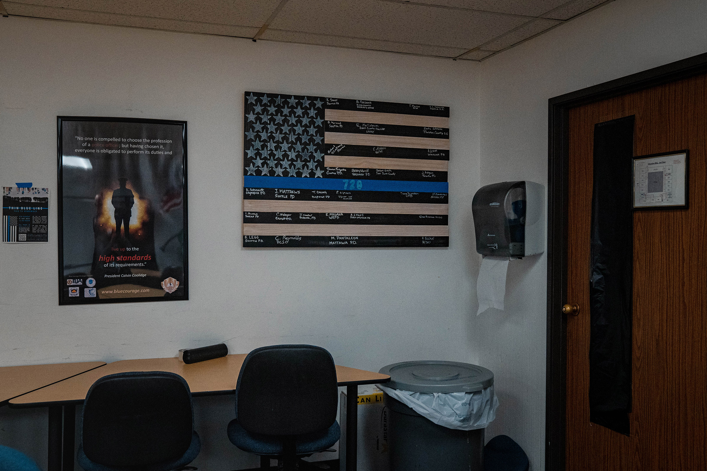 A thin blue line flag poster on display in an out-of-use classroom.