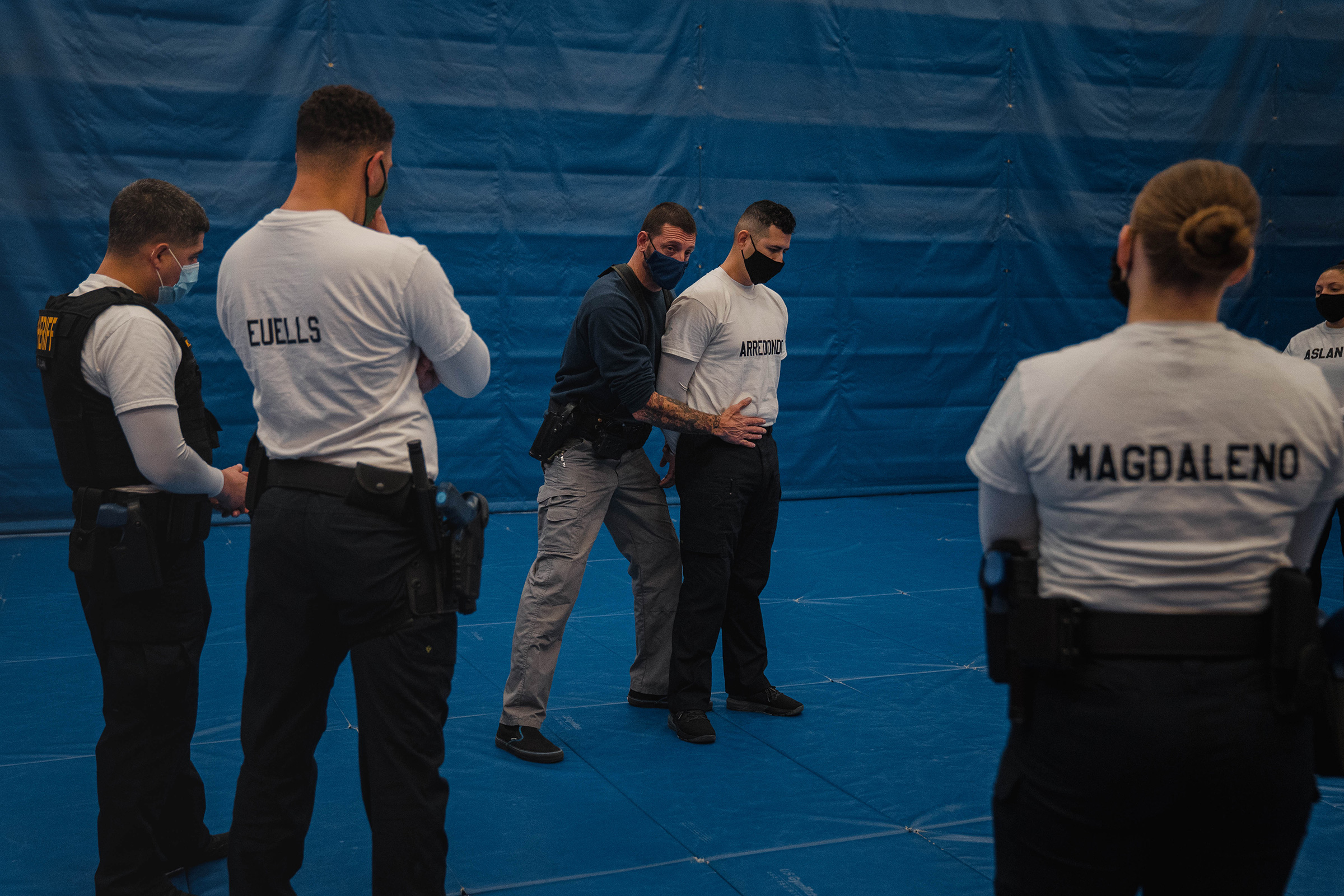 Instructor Javier Sola teaches frisking and handcuffing methods to future law enforcement officers at the state-run training facility in Washington state.