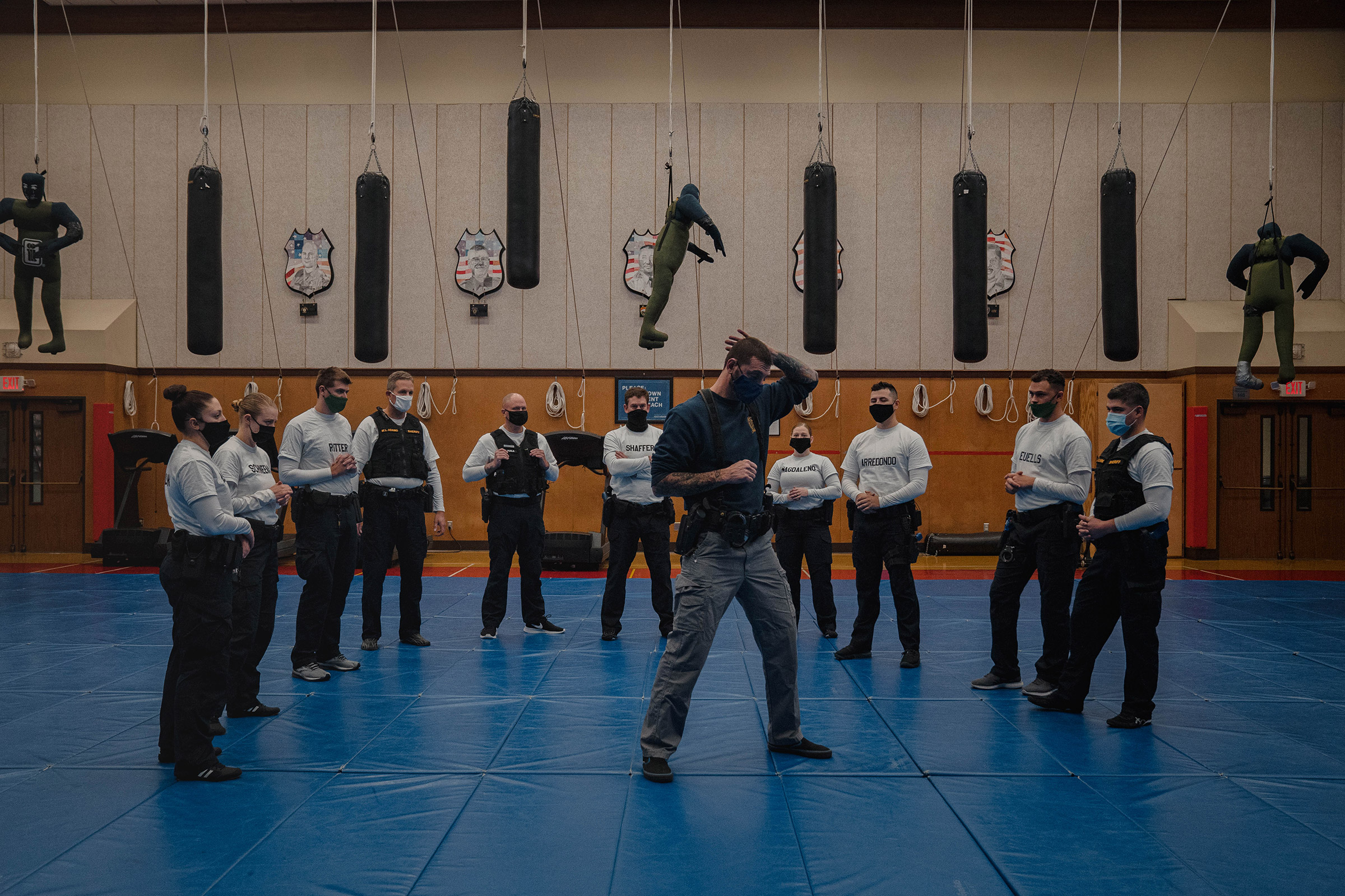 With punching bags and dummies overhead, instructor Javier Sola teaches frisking and handcuffing techniques to recruits at the Washington State Criminal Justice Training Commission facility in Burien, Wash., on Oct. 22. Washington State is one of the few places in the U.S. that requires all recruits to go through the state-run Basic Law Enforcement Academy, except for those becoming state patrol officers, a system that advocates of police reform support.
