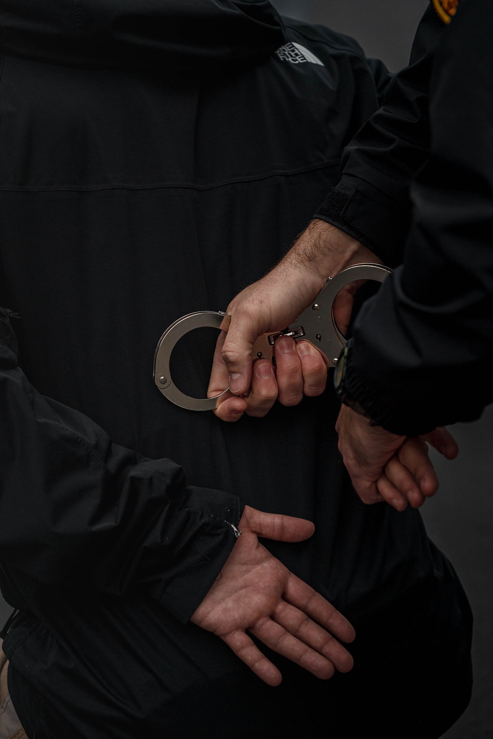 Police recruits practice handcuffing a suspect during a patrol tactics exercise.