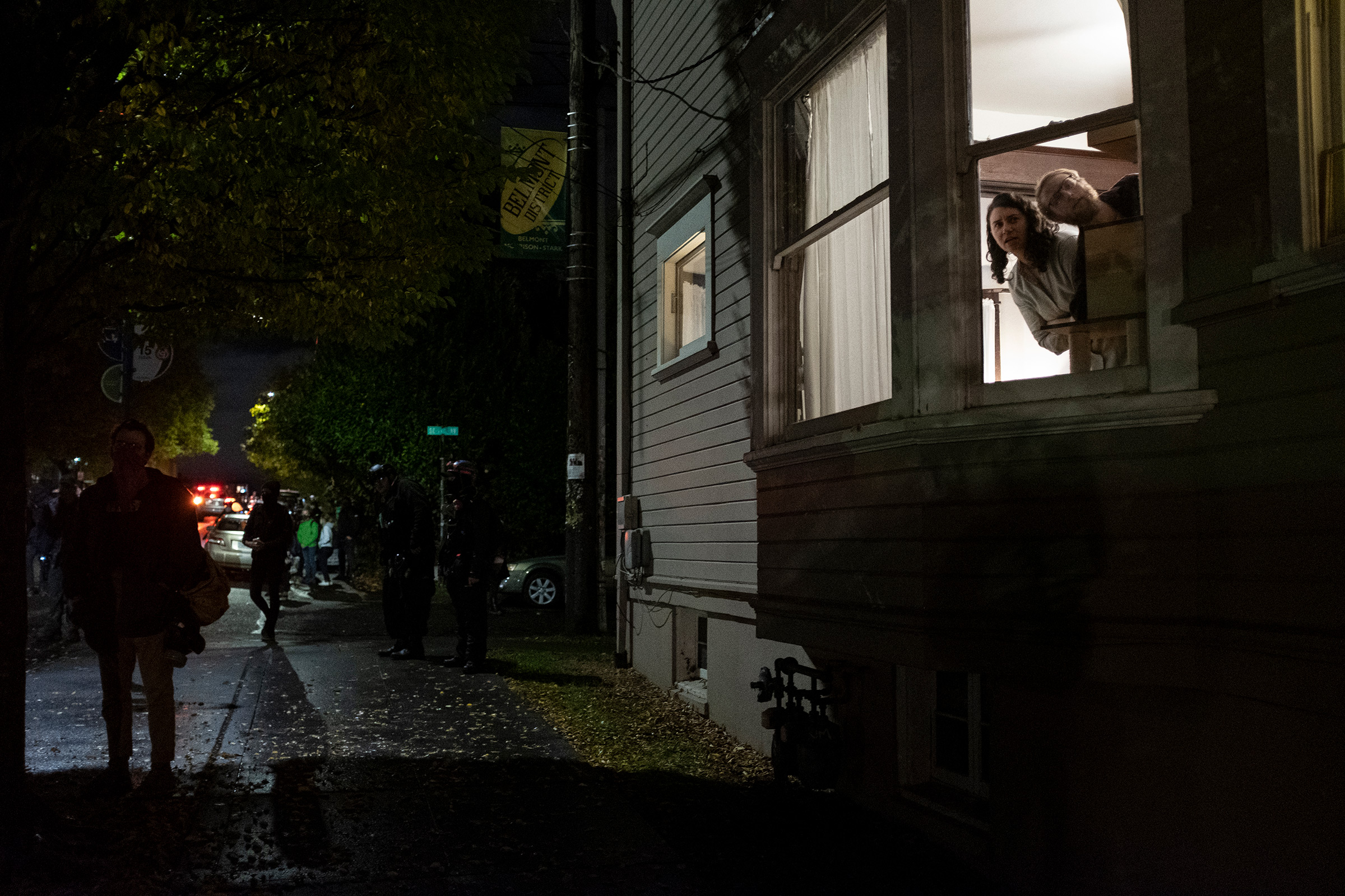 Residents watch a Black Lives Matter protest march through their neighborhood on election day in Portland, Ore., Nov. 3, 2020.