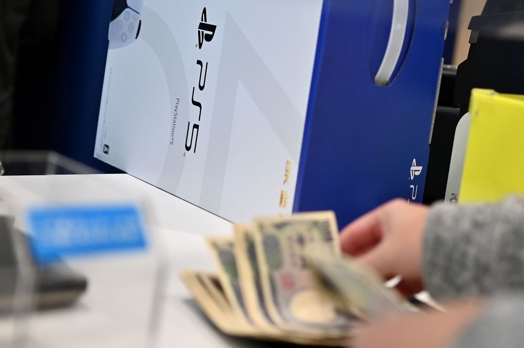 A customer buys the new Sony PlayStation 5 gaming console on the first day of its launch, at an electronics shop in Kawasaki, Kanagawa prefecture on November 12, 2020.