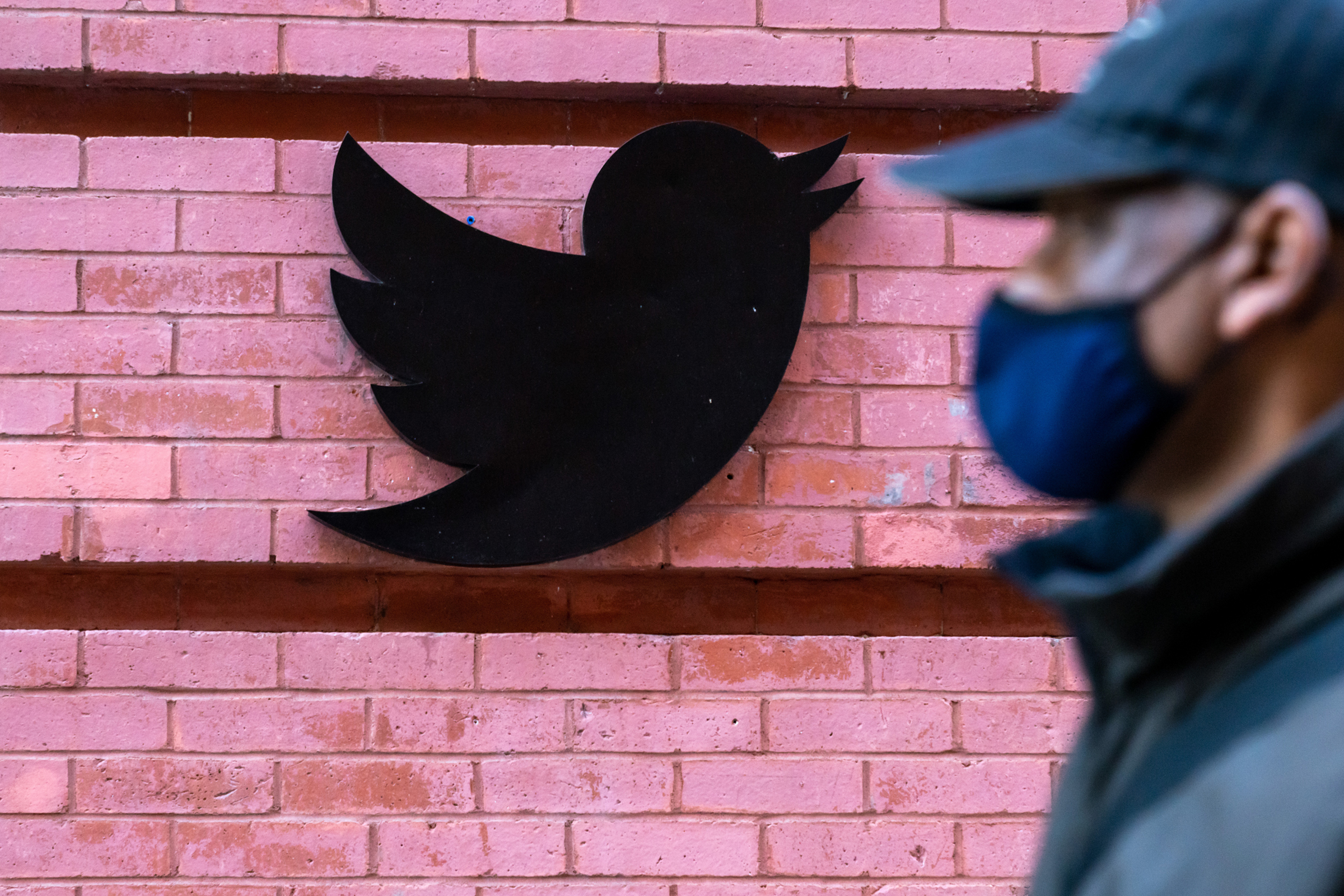 A man wearing a face mask walks past a Twitter logo outside their New York City headquarters on Oct. 14, 2020.
