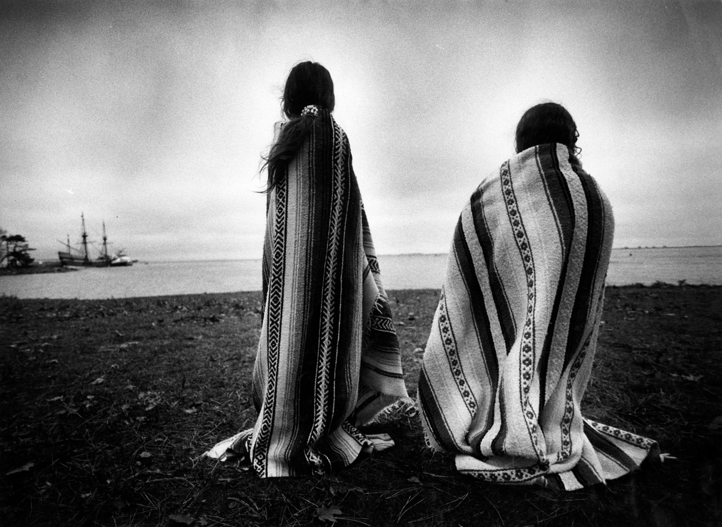 Weetoomoo Carey, 8, left, and Jackolynn Carey, 5, Wampanoag Nipmucs from Mashpee, look across to the Mayflower replica anchored near Plymouth Rock on Nov. 26, 1991. They were with a group of Native Americans gathered for a day of mourning in response to the Pilgrims' Thanksgiving