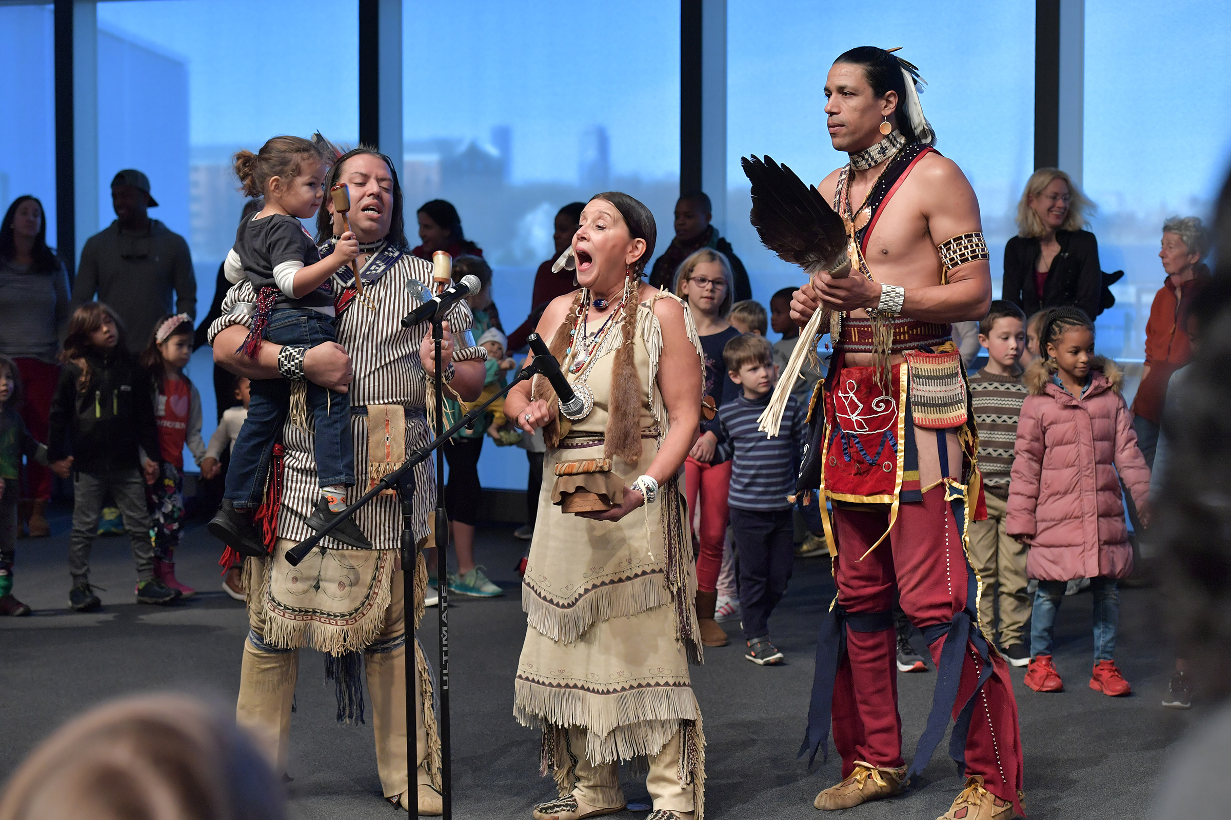 The Wampanoag Nation Singers and Dancers, including Jonathan James-Perry (L) and Kitty Hendricks Miller (C) perform at the John F. Kennedy Presidential Library and Museum on Nov. 29, 2019 in Boston to commemorate Native American Heritage Month