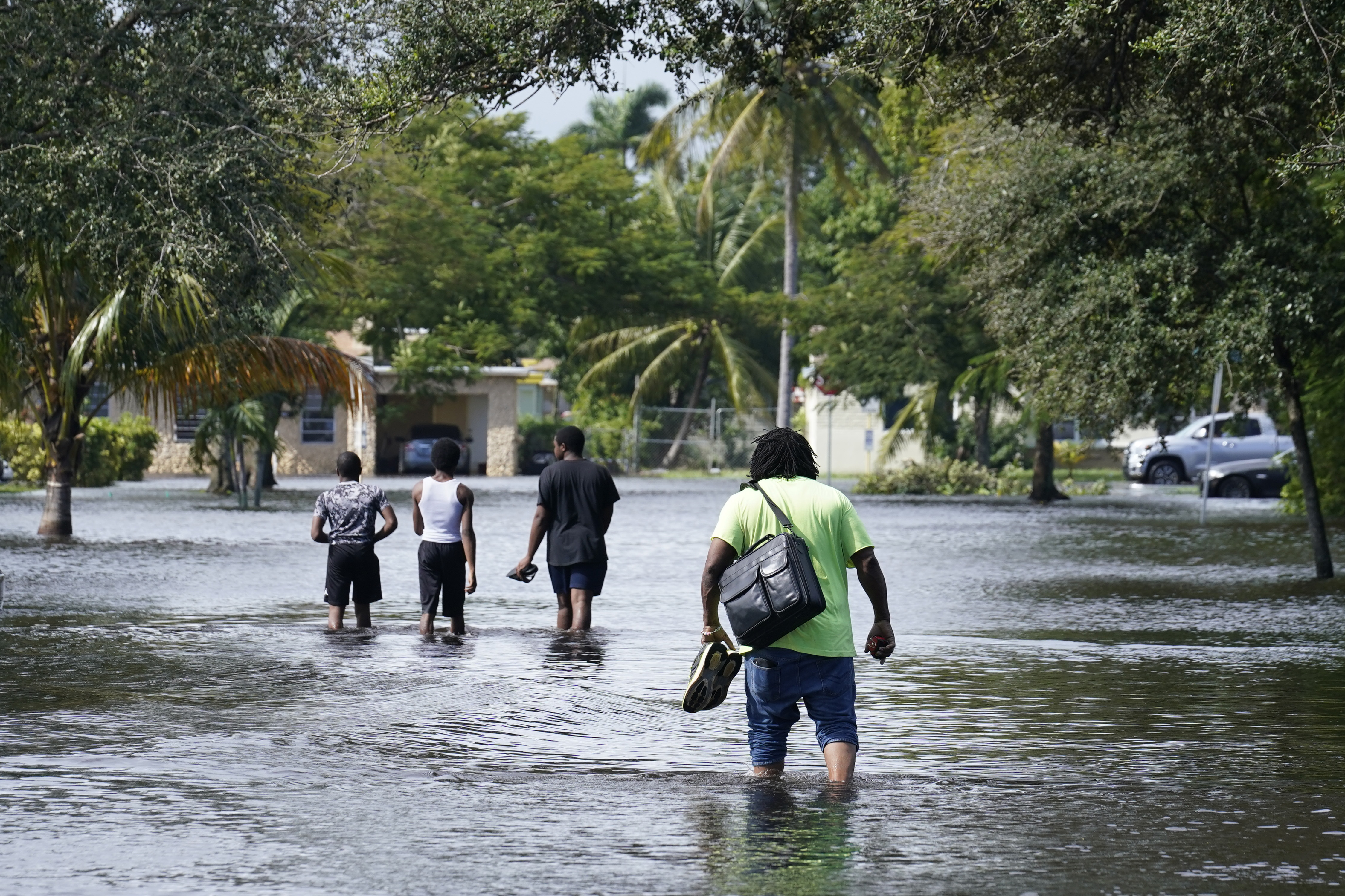 Residents walk a flooded street to reach their homes, Monday, Nov. 9, 2020 in Fort Lauderdale, Fla.
