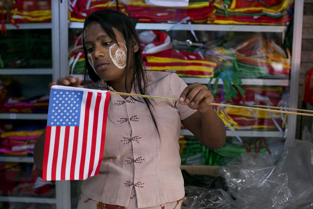 A Myanmar woman fixes an American flag as Yangon prepares for the first visit of President Barack Obama on Nov. 18, 2012.