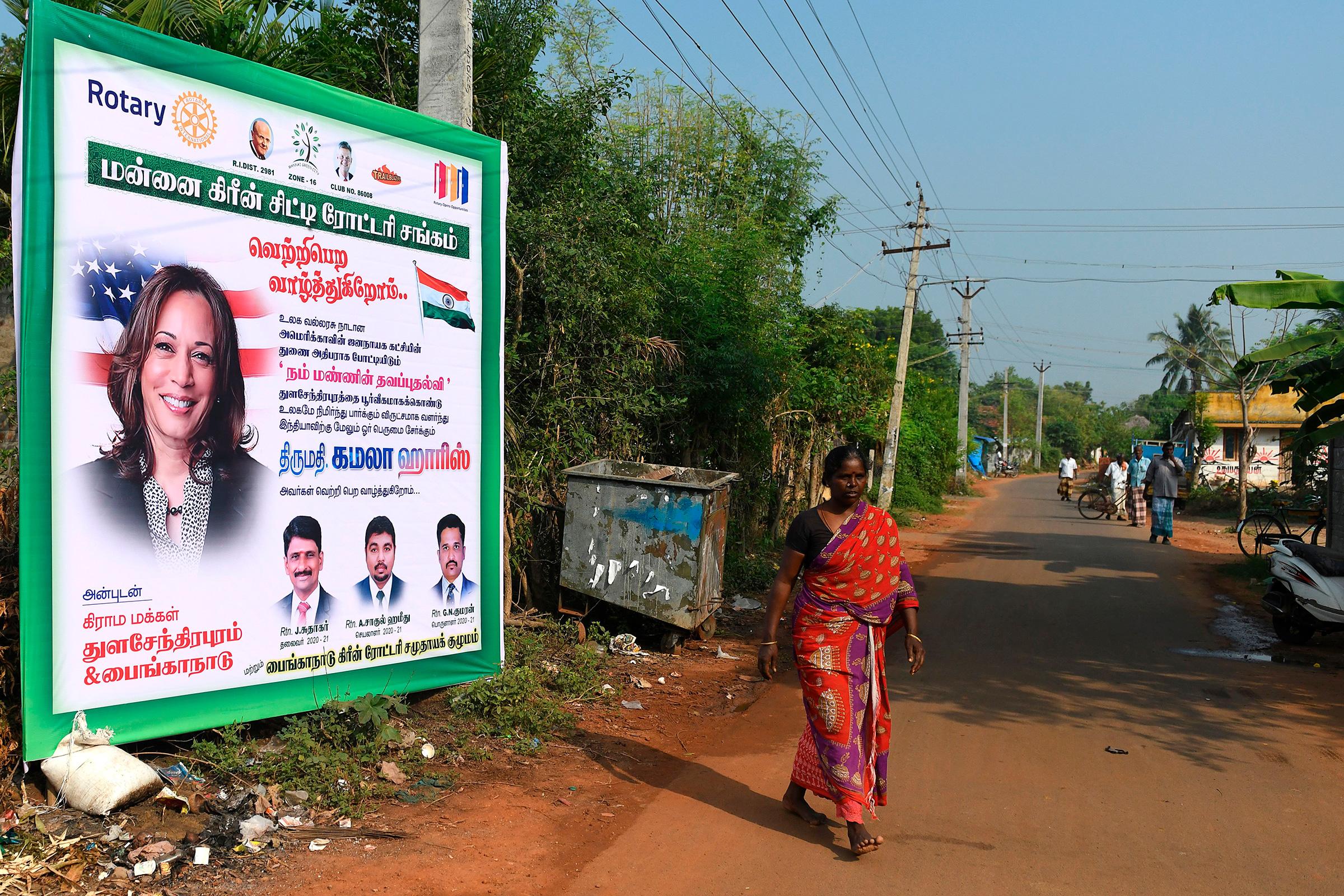 A woman walks past a poster of U.S. vice presidential candidate Kamala Harris at her ancestral village of Thulasendrapuram, Tamil Nadu, on Nov. 3.