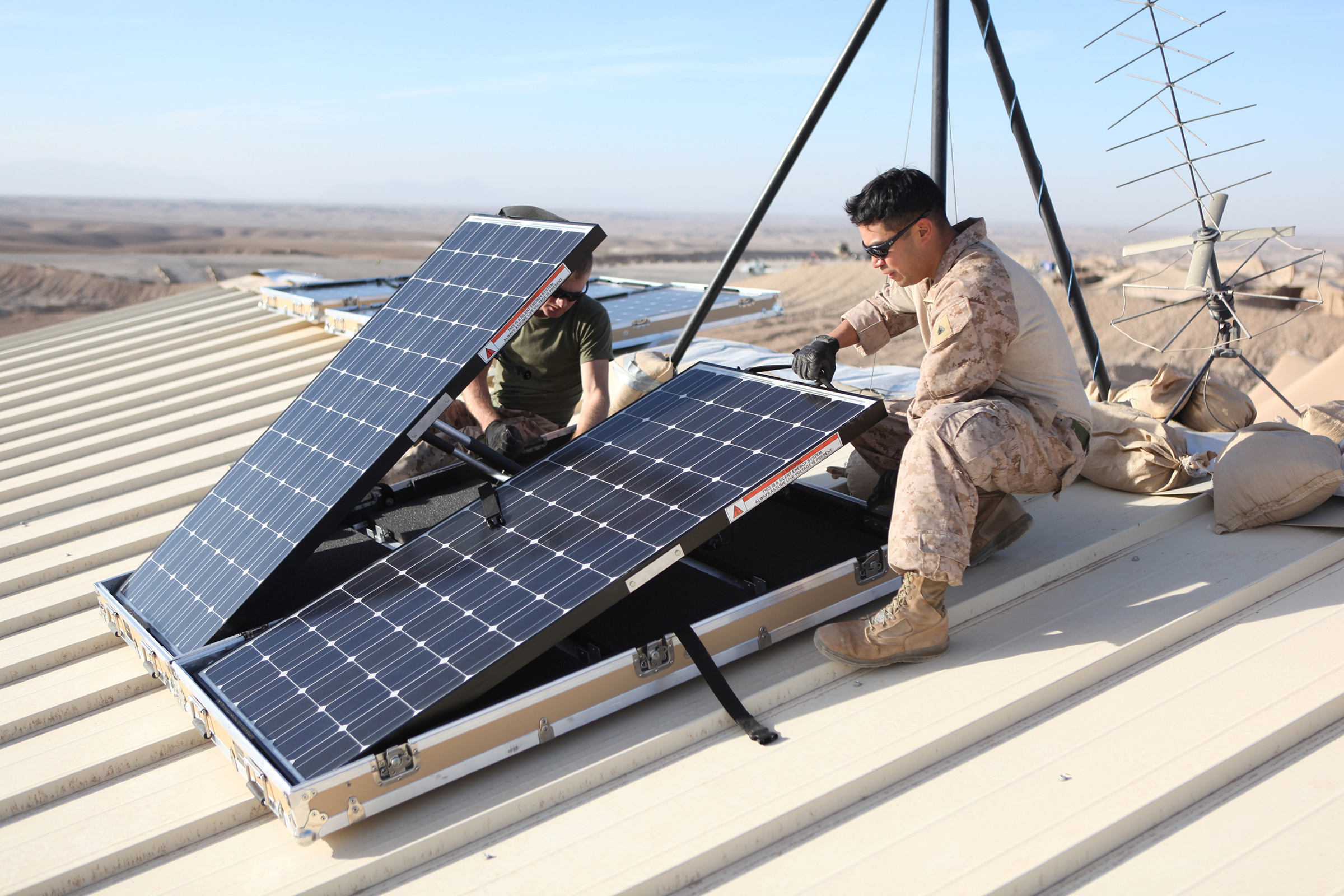 U.S. Marine Corps Corporal Robert G. Sutton (L) and Corporal Moses E. Perez install new solar panels on Combat Outpost Shukvani, Helmand province, Afghanistan, on Nov. 19, 2012