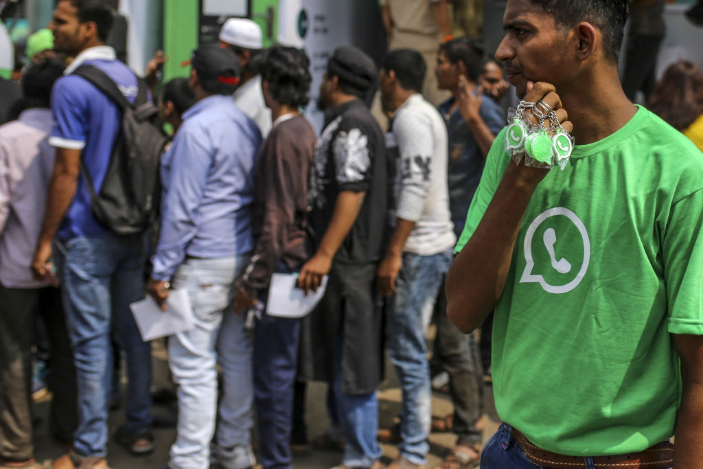 A WhatsApp ambassador holds branded key chains as spectators stand in line during a roadshow for WhatsApp's messaging service and Reliance Jio Infocomm Ltd.'s wireless network in Pune, India, on Thursday, Oct. 25, 2018.