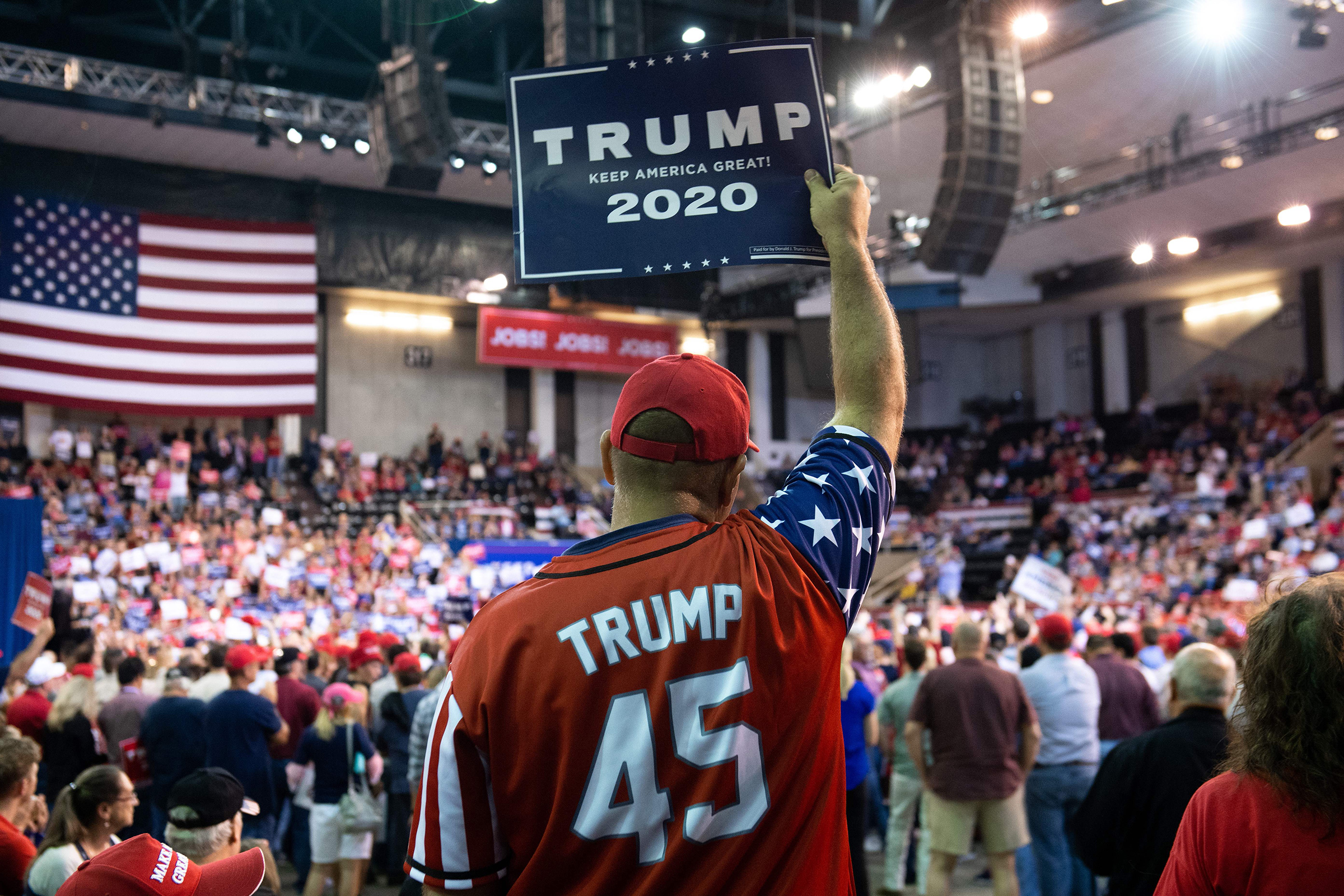 A Trump supporter holds up a sign as the US president speaks during a  Keep America Great  rally at Sudduth Coliseum in Lake Charles, La. on Oct. 11, 2019