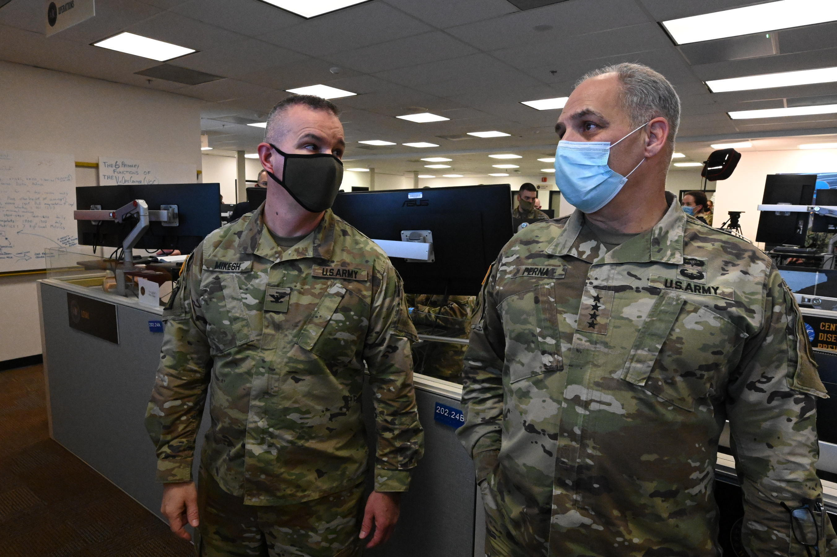 Operation Warp Speed information technology lead Colonel R.J. Mikesh speaks with General Gus Perna in the Vaccine Operations Center.