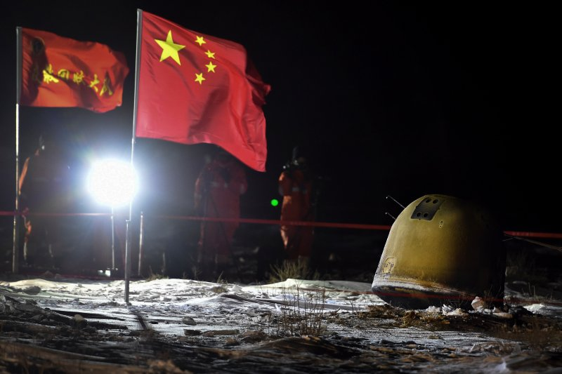 In this photo released by Xinhua News Agency, recovery crew members film the capsule of the Chang'e 5 probe after its successful landed in Siziwang district, north China's Inner Mongolia Autonomous Region on Thursday, Dec. 17, 2020.