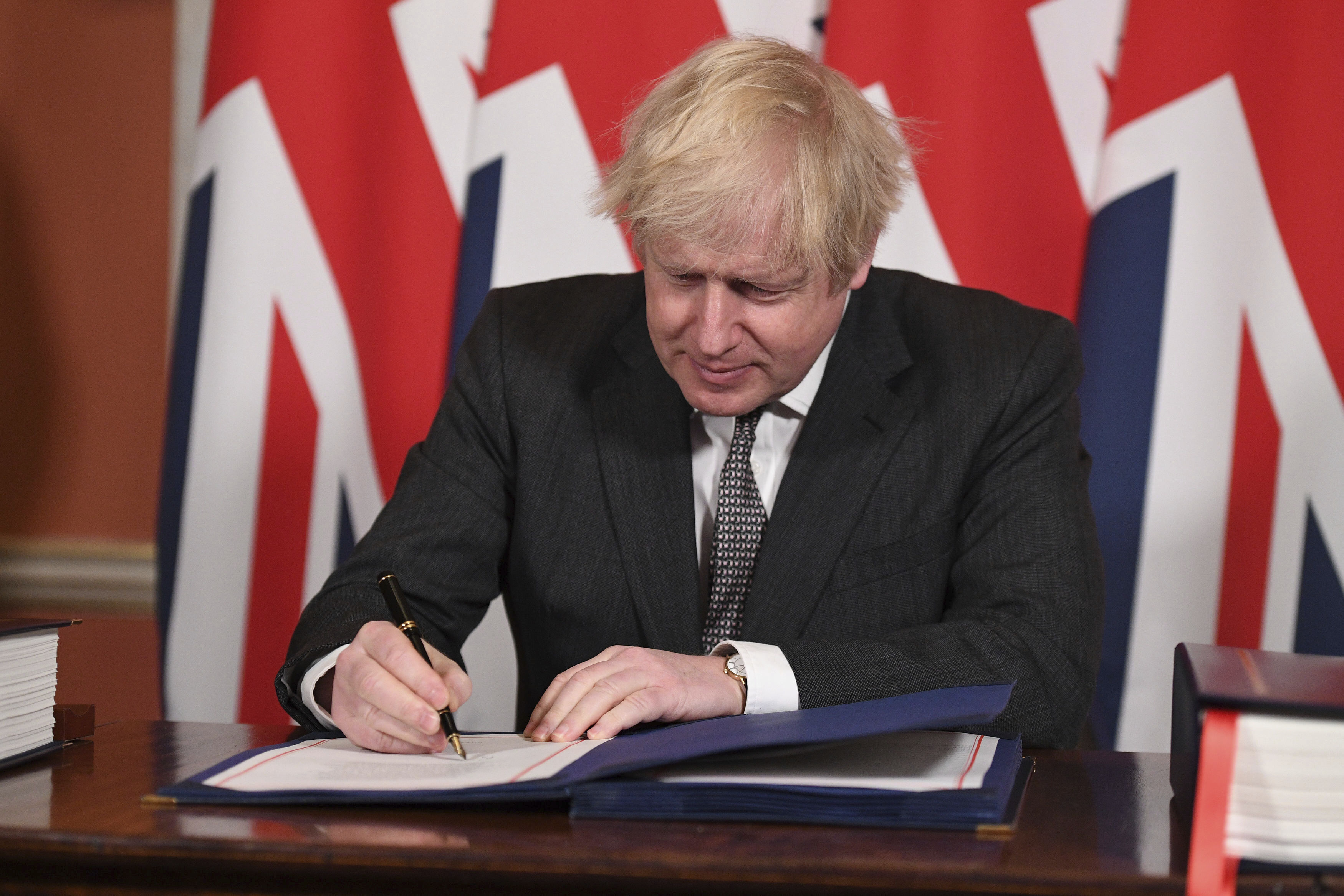 Britain's Prime Minister Boris Johnson signs the EU-UK Trade and Cooperation Agreement at 10 Downing Street, London Wednesday Dec. 30, 2020.