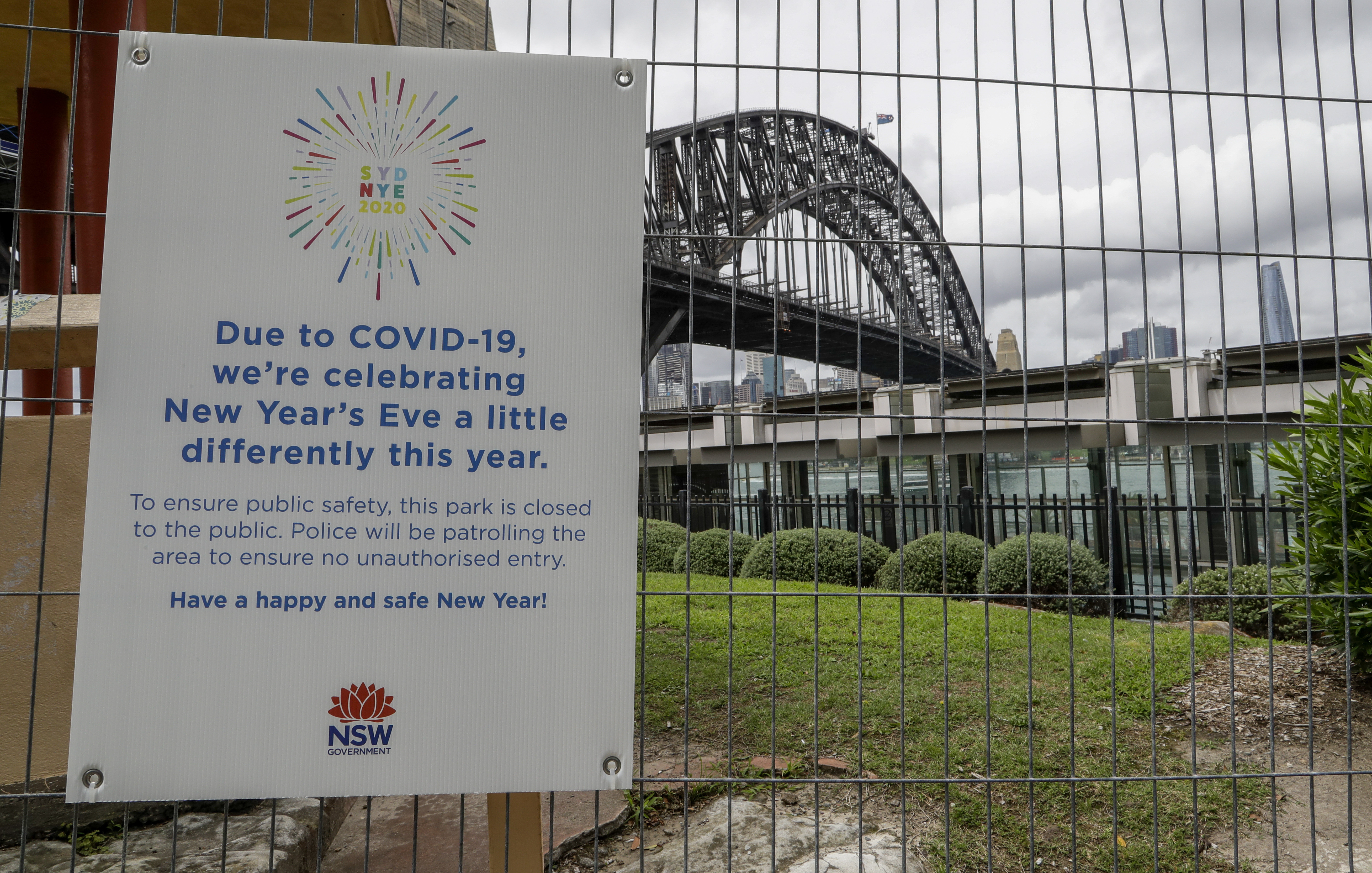 A signs adorns a security fence near the harbour foreshore ahead of New Years Eve in Sydney, Australia, Thursday, Dec. 31, 2020.