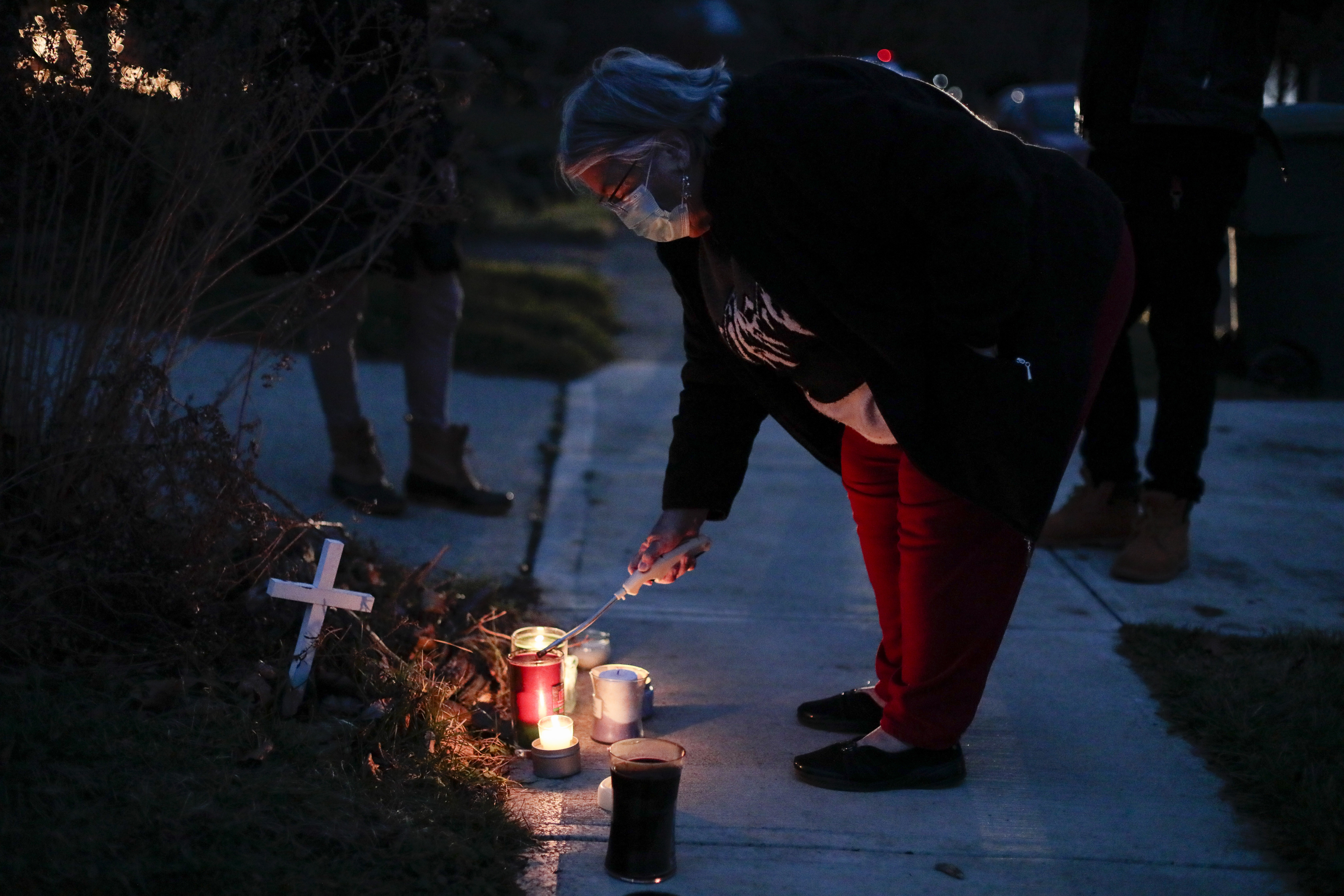 A neighbor lights a candle at a small memorial near the site of the fatal police shooting of Andre Hill on Wednesday, Dec. 23, 2020 on Oberlin Drive in Columbus, Ohio. Hill, 47, was shot and killed by Columbus Division of Police officer Adam Coy after responding to a suspicious vehicle call around 1:30 a.m., on Tuesday, Dec. 22, 2020 in the 1000 block of Oberlin Drive. Body camera footage released Wednesday shows Andre Hill, a 47-year-old Black man, emerging from a garage and holding up a cellphone in his left hand seconds before he is fatally shot by a Columbus police officer.