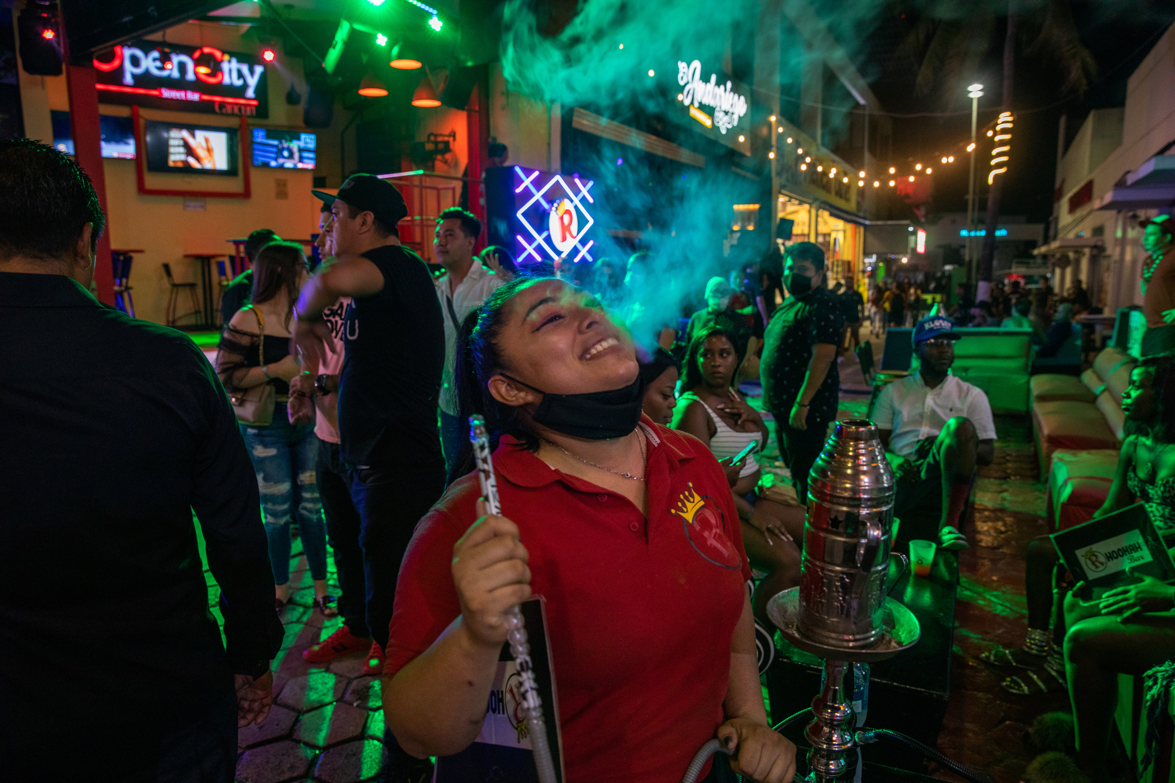 Tourists smoke hookah at local bars in the Cancún's popular nightlife district on Oct. 17. After a drop in travel because of the pandemic, American tourists are again flooding the city's streets and beaches.