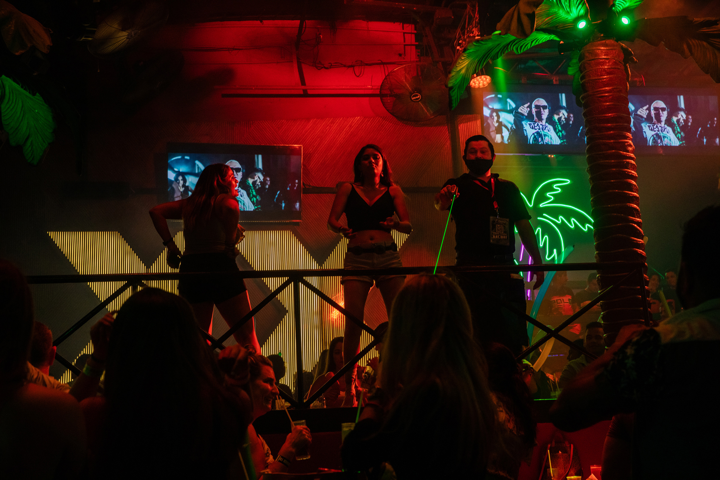 Revelers dance at a club in Cancún's nightlife district on Oct. 17. Despite the pandemic still raging in Mexico, few tourists wear masks when packed together inside the city's open-air clubs.
