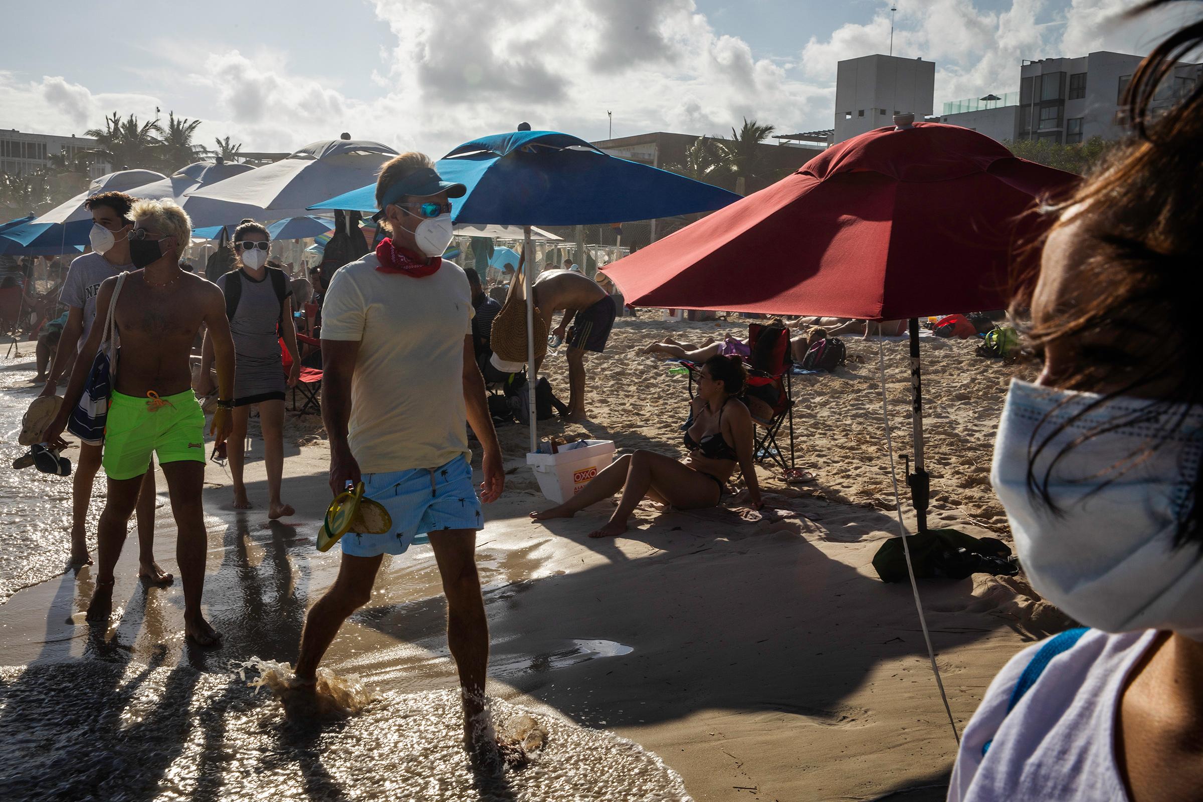 Tourists stroll on the beach in Playa del Carmen, Quintana Roo, Mexico, on Nov. 22, 2020.