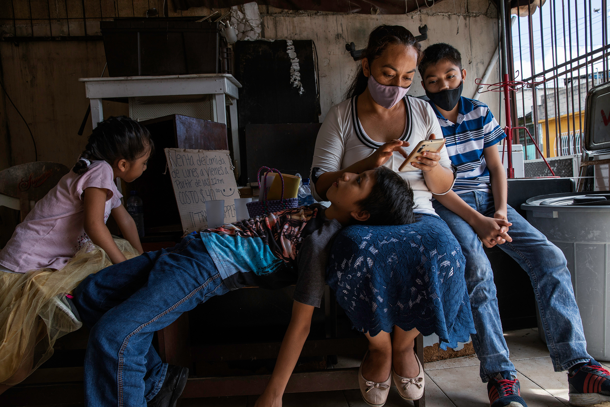 Magali, 35, and her sons wait outside Huellas de Pan Association, a a nonprofit working on food security, before a healthy-nutrition workshop in one of the poorest neighborhoods in Cancún.