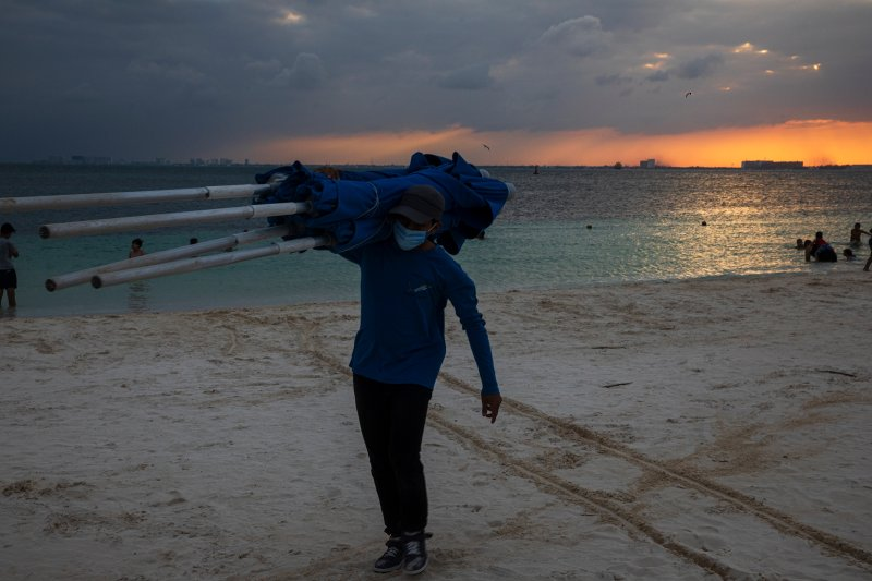 A worker collects beach umbrellas at the end of the day at Isla Mujeres, Quintana Roo, on Dec. 2.