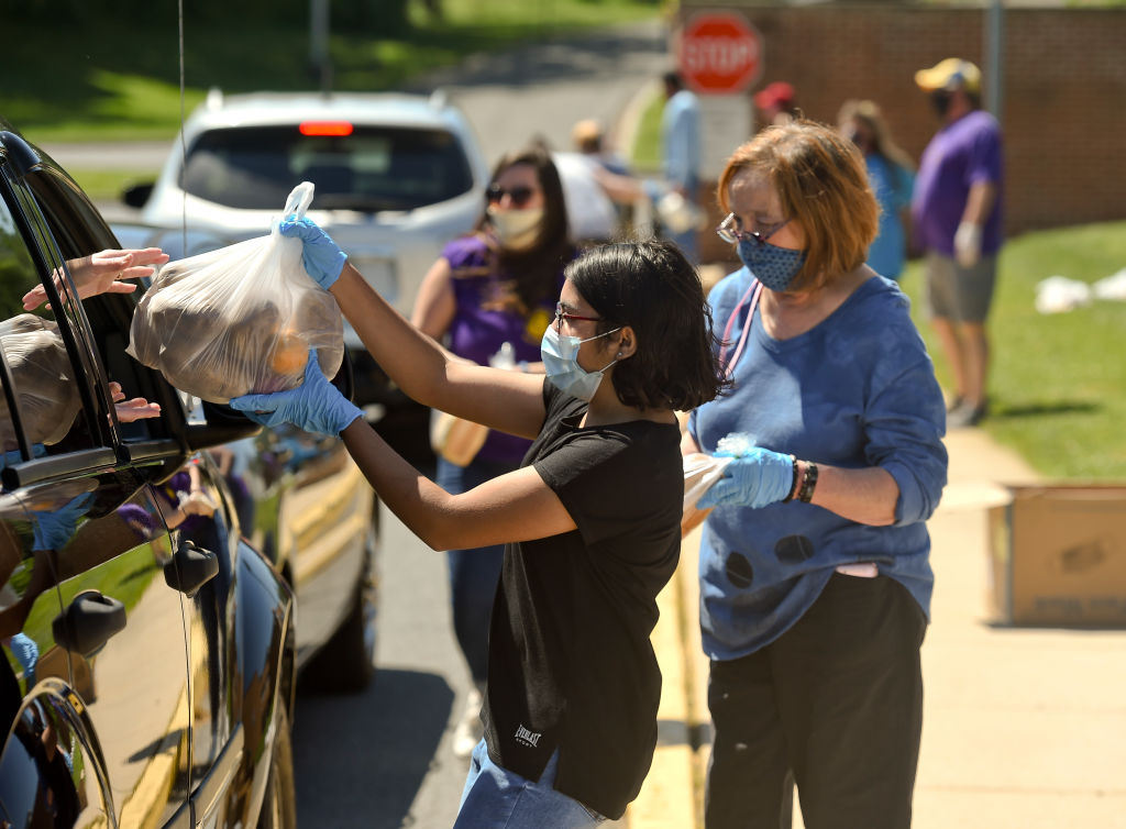 People receive bags of food at a drive-through food distribution event in Cumru, Penn. on May 30.