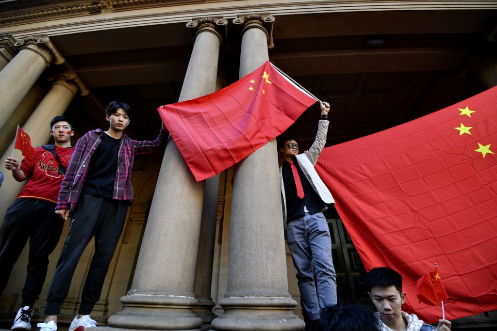 Pro-China activists hold up their national flag in Sydney on August 17, 2019, as they rally against ongoing protests in Hong Kong.