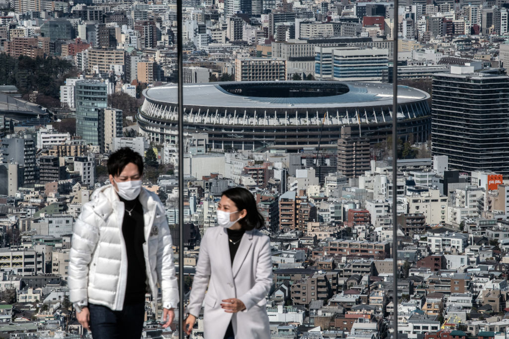 A couple wearing face masks walks away after viewing the New National Stadium, the main stadium for the Tokyo 2020 Olympics, as they visit the Shibuya Sky observation deck on March 24, 2020 in Tokyo, Japan.