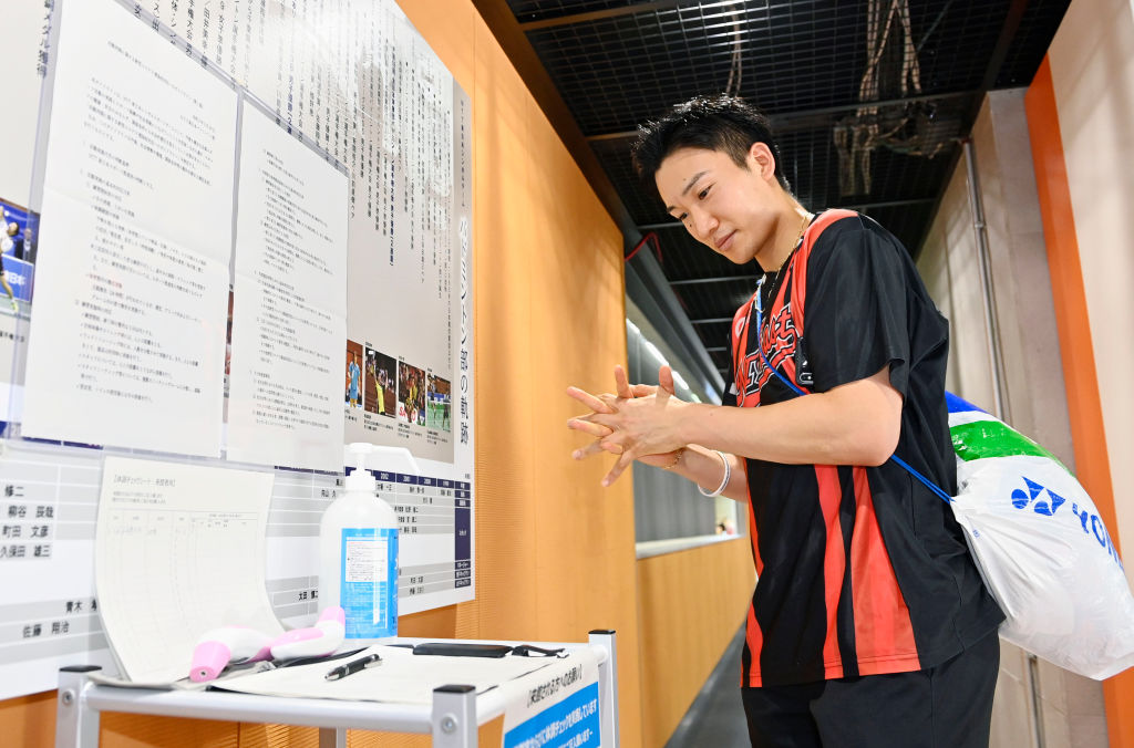 Japan's badminton player Kento Momota disinfects his hands prior to a training session in Tokyo on June 26, 2020. He has vowed to bring home Gold at the postponed Tokyo Games.