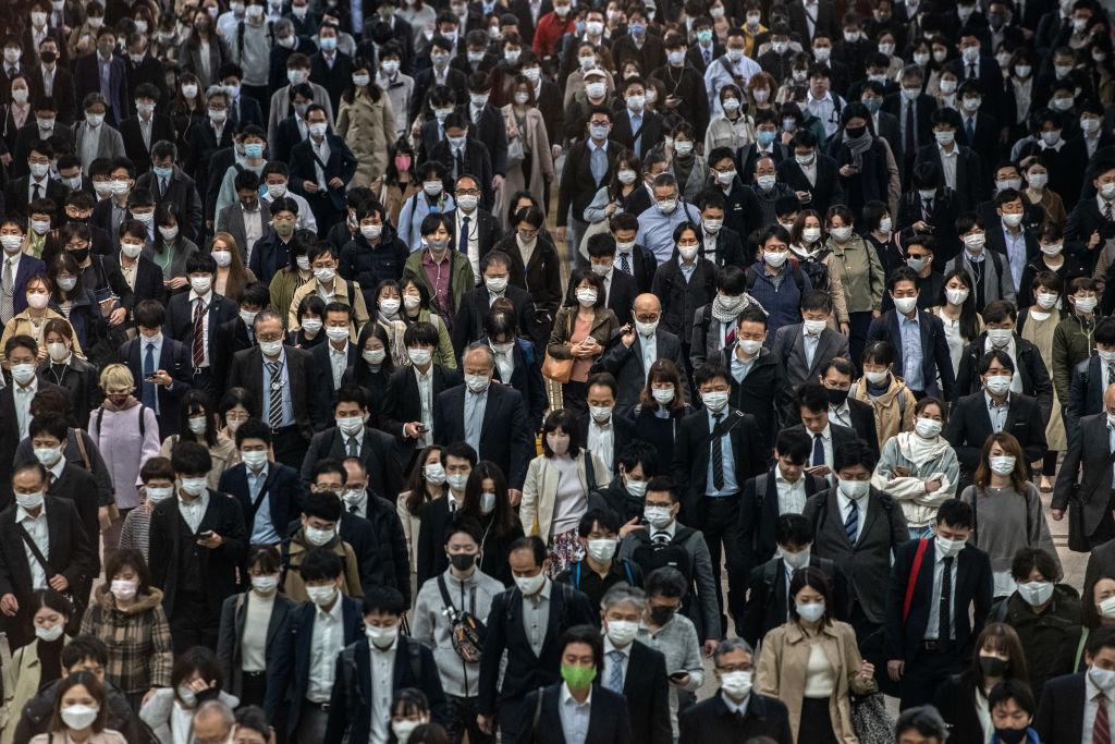 Commuters, mostly wearing face masks, walk through Shinagawa train station on November 18, 2020 in Tokyo, Japan.