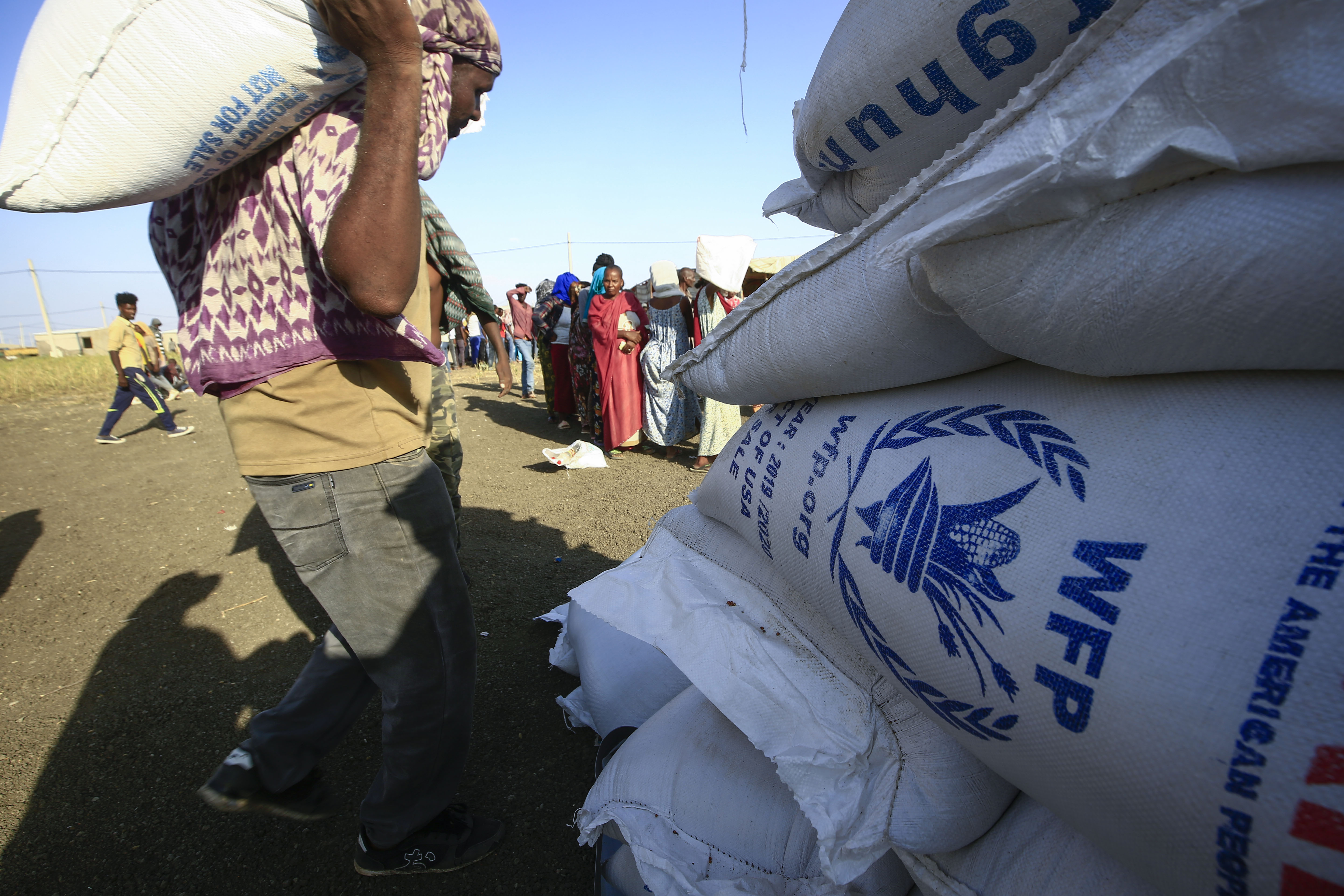 Ethiopian refugees who fled fighting in the Tigray Region watch workers unload World Food Programme food aid at the Village 8 border reception center in Sudan's eastern Gedaref State, on November 20, 2020.