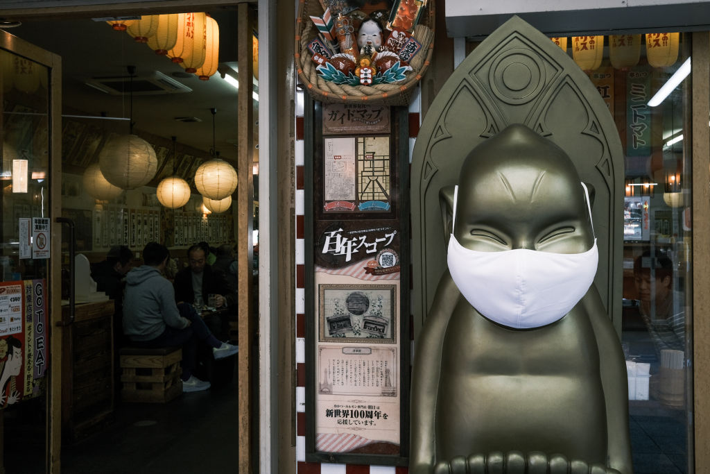 A statue in front of a restaurant wears a protective mask in the Shinsekai shopping district of Osaka, Japan, on Sunday, Nov. 29, 2020.
