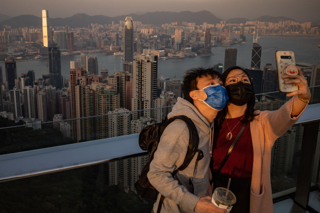 A couple wearing protective masks take a selfie at an observation deck at Victoria Peak on December 2, 2020 in Hong Kong, China.