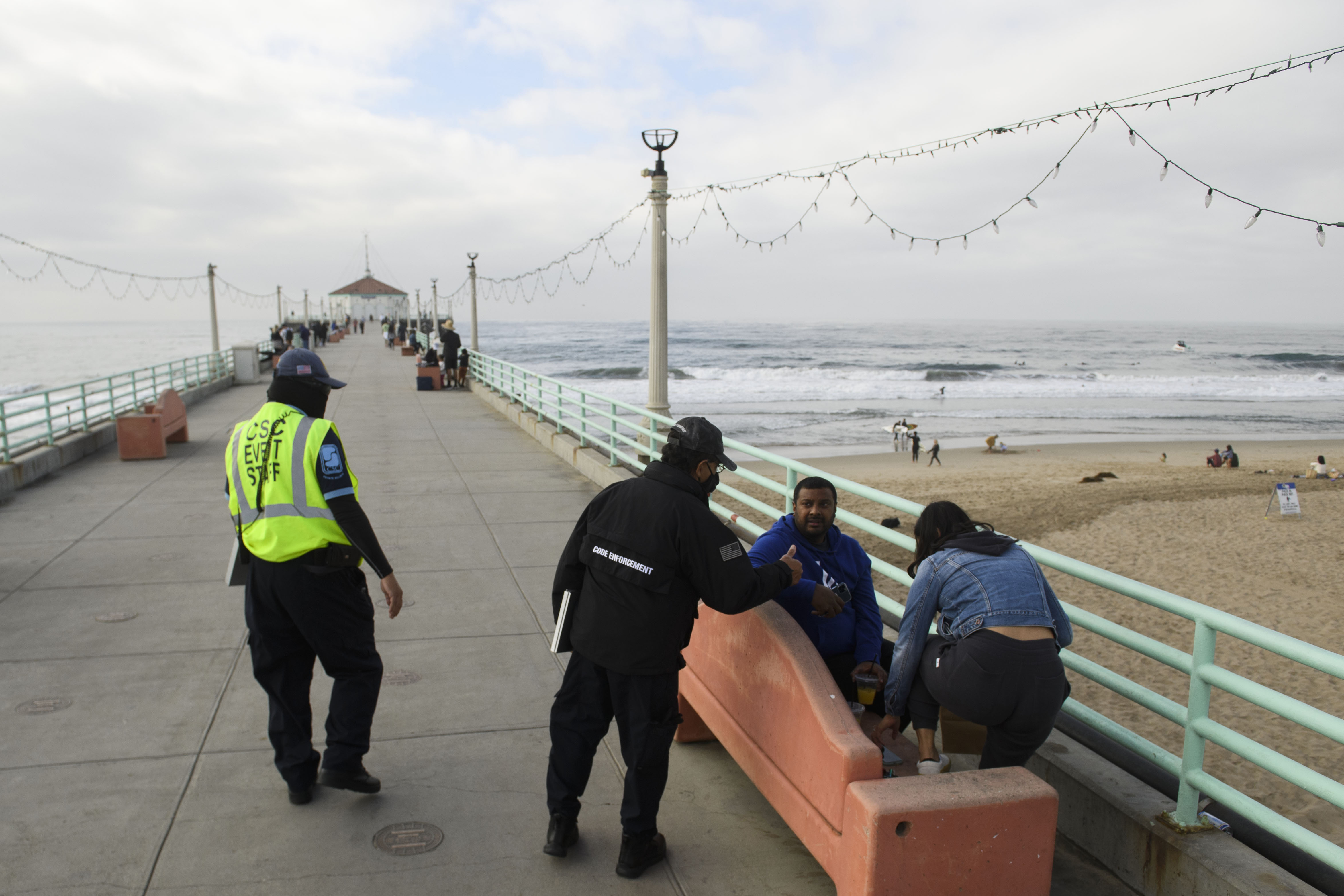 City workers enforce COVID-19 mask restrictions on the pier in Manhattan Beach, Calif., on Dec. 12, 2020.