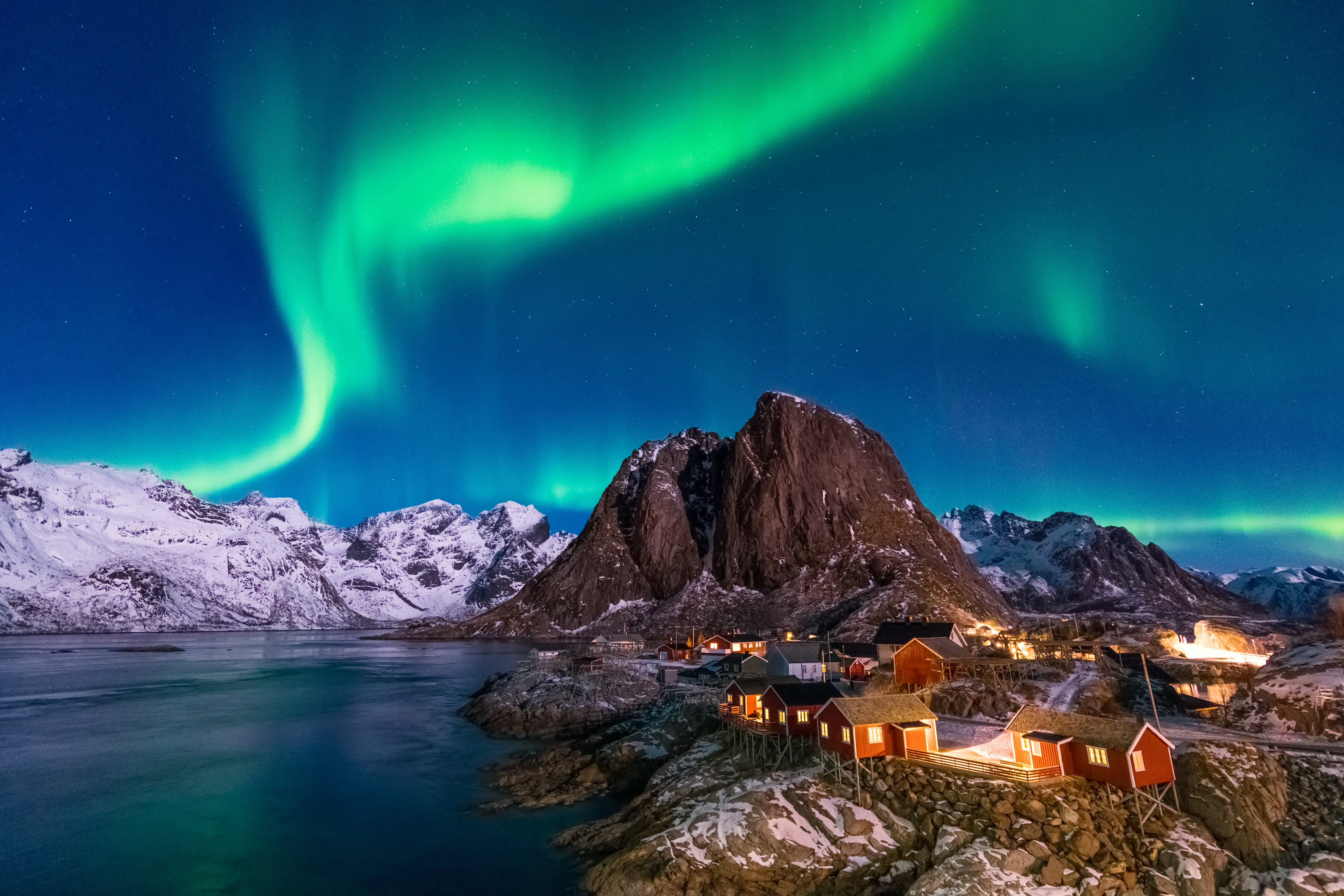 Northern Lights (Aurora Borealis) above the iconic view of a picturesque fishing village in Hamnoy (Hamnøy), Lofoten islands, Norway in winter.