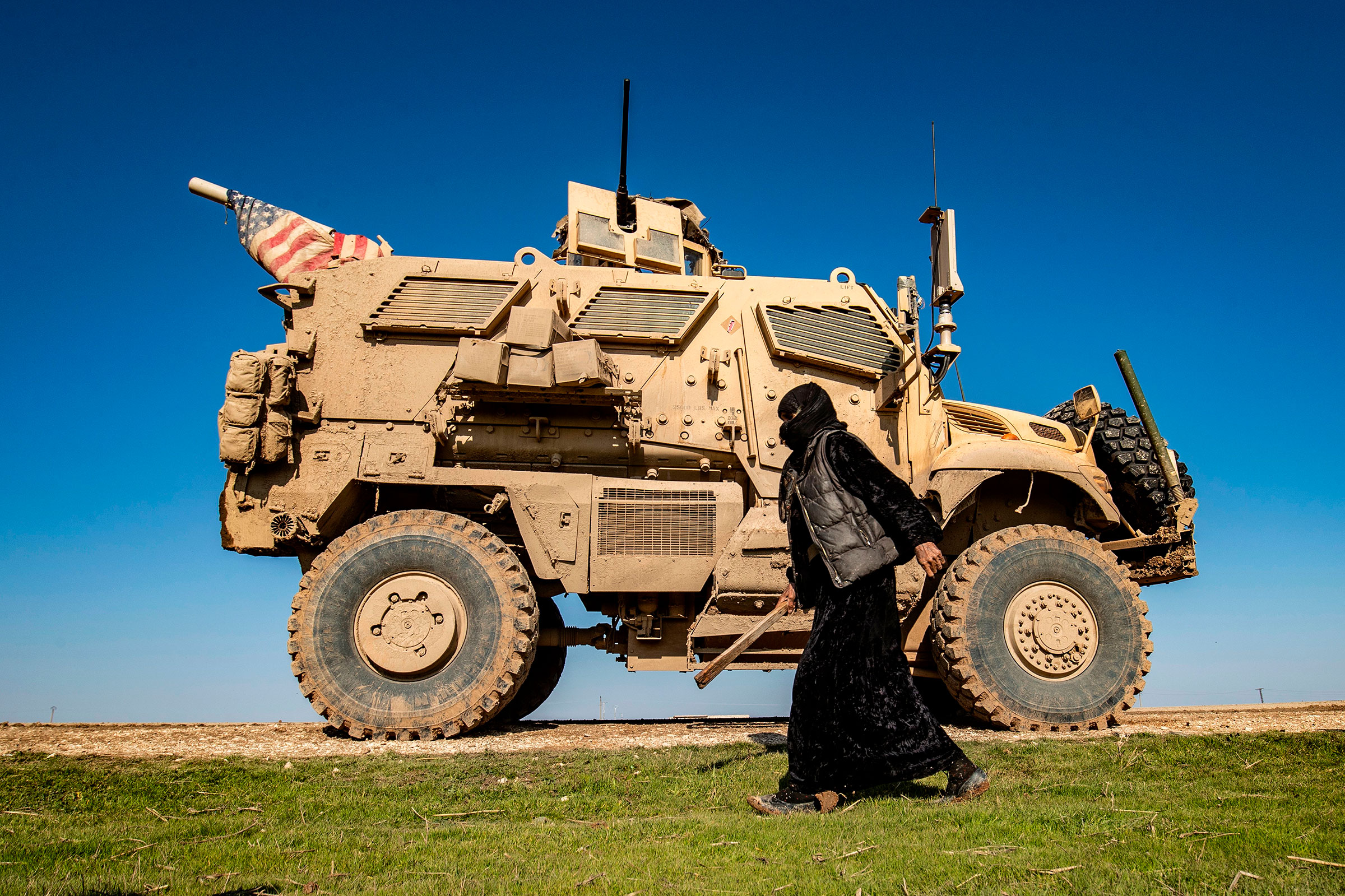 A woman passes a U.S. military vehicle in northeast Syria on Jan. 22