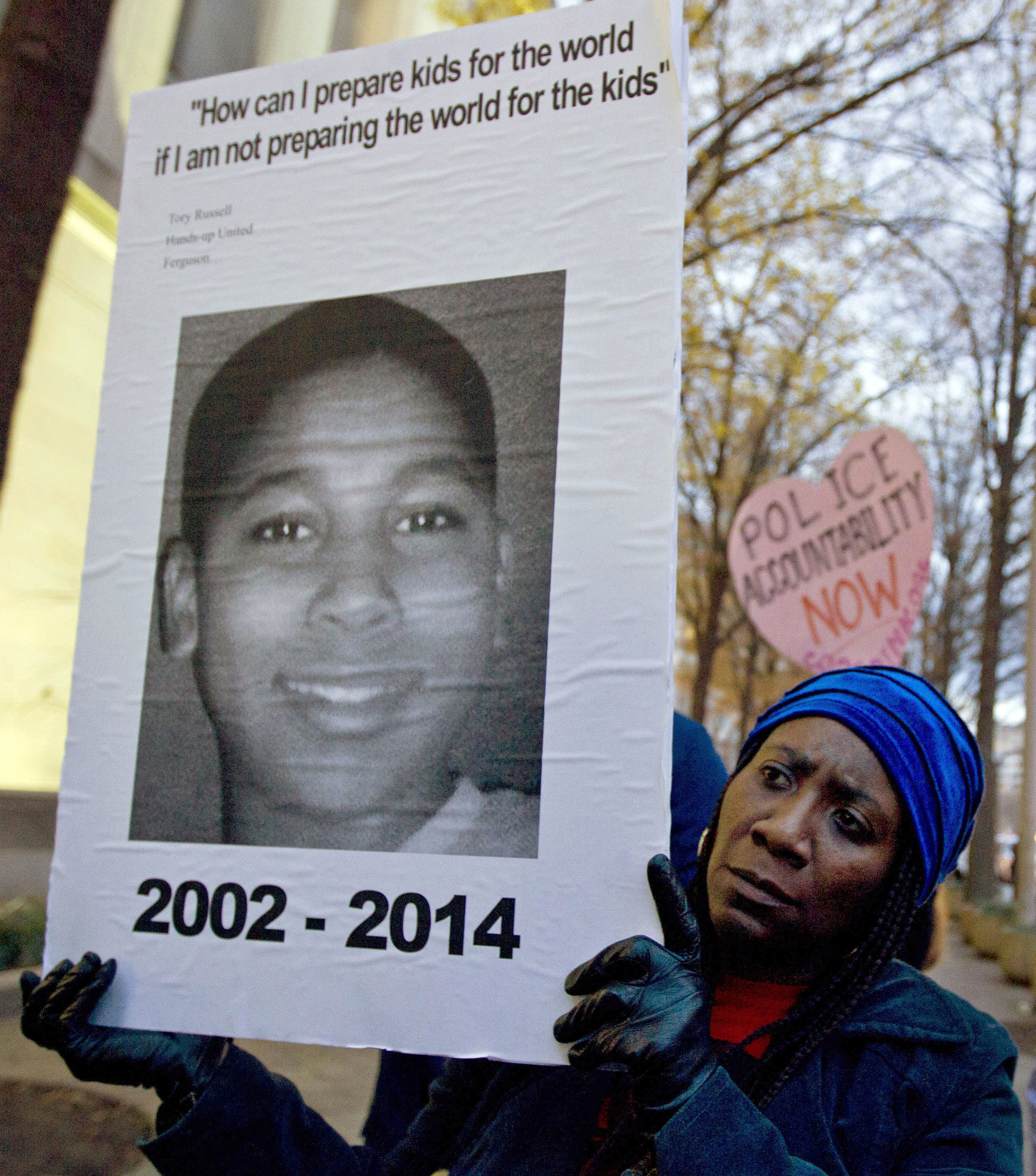 In this Dec. 1, 2014, file photo, Tomiko Shine holds up a picture of Tamir Rice, a 12-year-old boy fatally shot Nov. 22, 2014, by a rookie police officer in Cleveland, Ohio, during a protest in Washington, D.C.