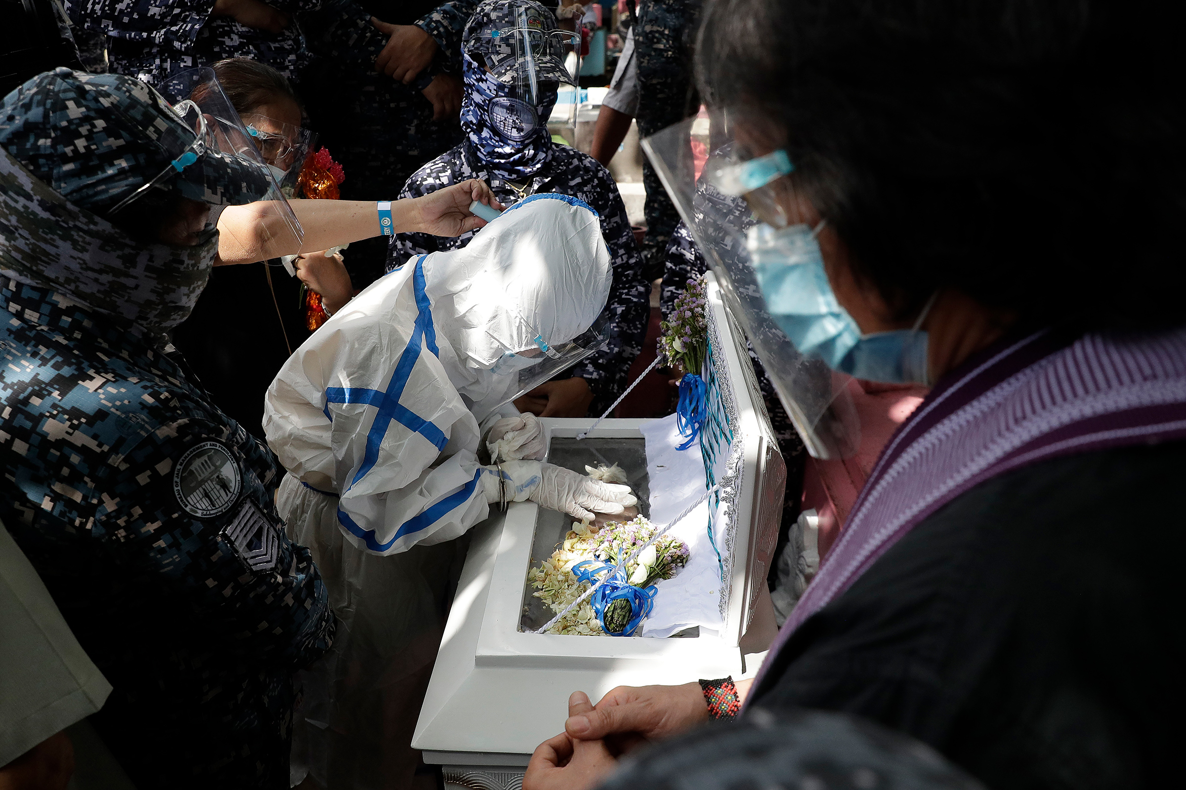 Detained left-wing activist Reina Mae Nasino, in handcuffs and wearing a protective suit to prevent the spread of coronavirus, touches the coffin of her three-month-old daughter, River, during funeral rites guarded by armed escorts at Manila North Cemetery on Oct. 16. The 23-year-old was among three activists arrested last year in a Philippine left-wing group's office, the Associated Press reported, and charged with the illegal possession of explosives and firearms; their lawyers alleged that the weapons were placed by police, which denied the accusation. A court allowed Nasino three hours to attend the burial of her baby, who died of acute gastroenteritis, the AP added, but critics decried her treatment.