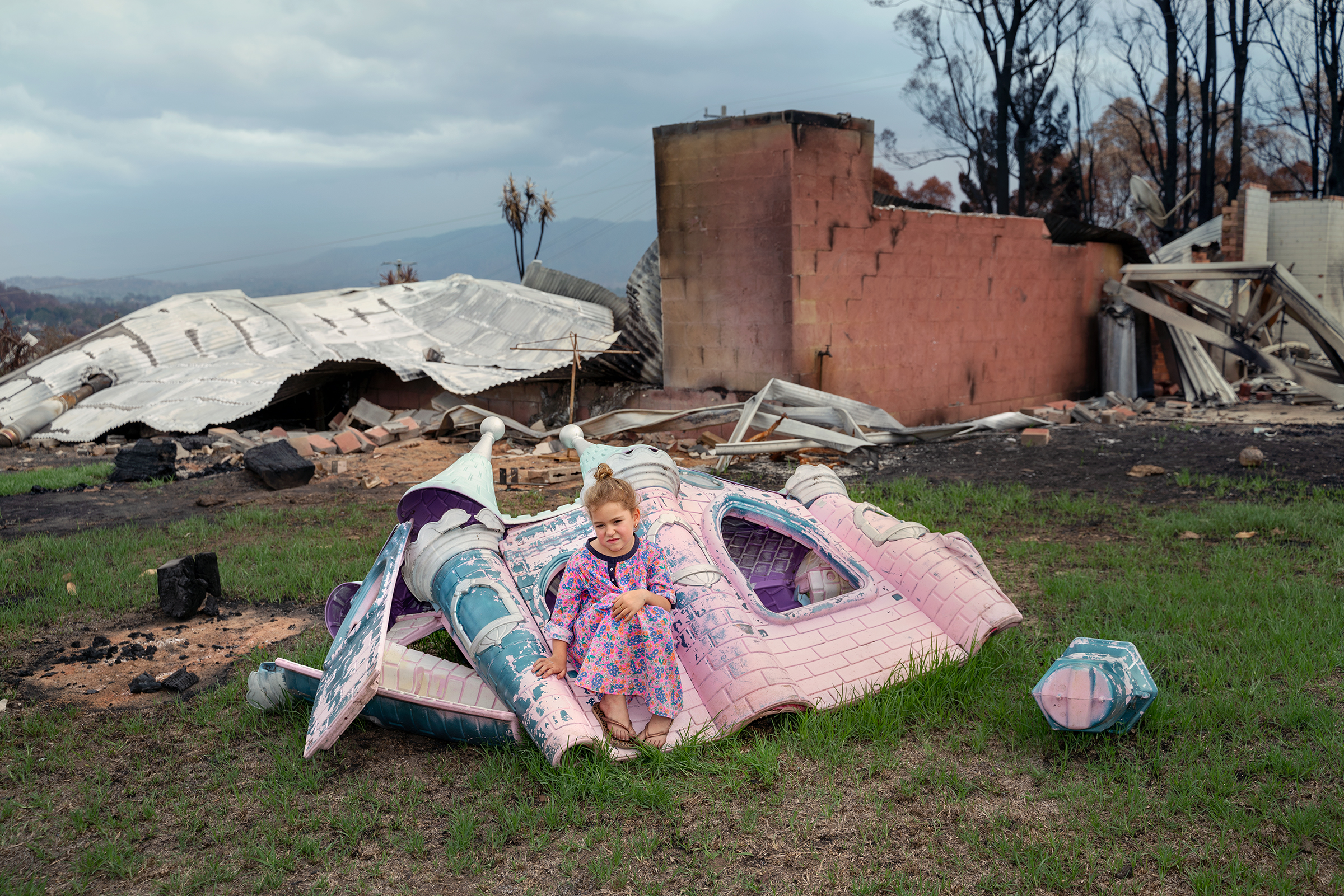 Sarah Rugendyke,7, sits on a play castle that was burned on her family's property in Cobargo on Jan. 20; an out-of-control bushfire devastated the tourist town about 240miles south of Sydney on NewYear's Eve.  Forgotten Country,  Feb. 3 issue.