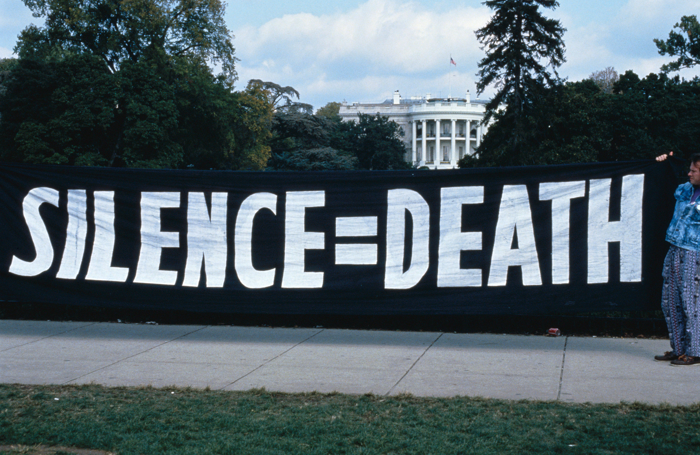 ACT UP activists hang a banner outside of the White House in Washington, D.C.