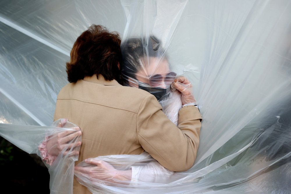 Olivia Grant, right, hugs her grandmother, Mary Grace Sileo, through a plastic drop cloth hung up on a clothesline in a backyard in Wantagh, N.Y., on May 24.