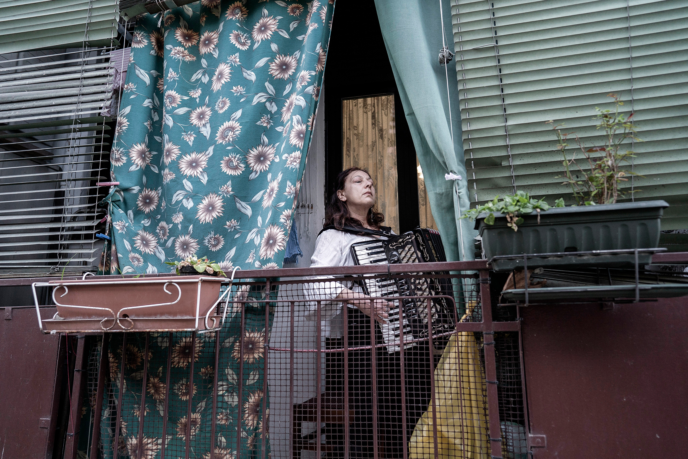 A woman plays music from her balcony in Milan on March 13. Italians remained essentially under house arrest as the nation—the European front in the global fight against coronavirus—had ordered extraordinary restrictions on their movement to prevent its spread.