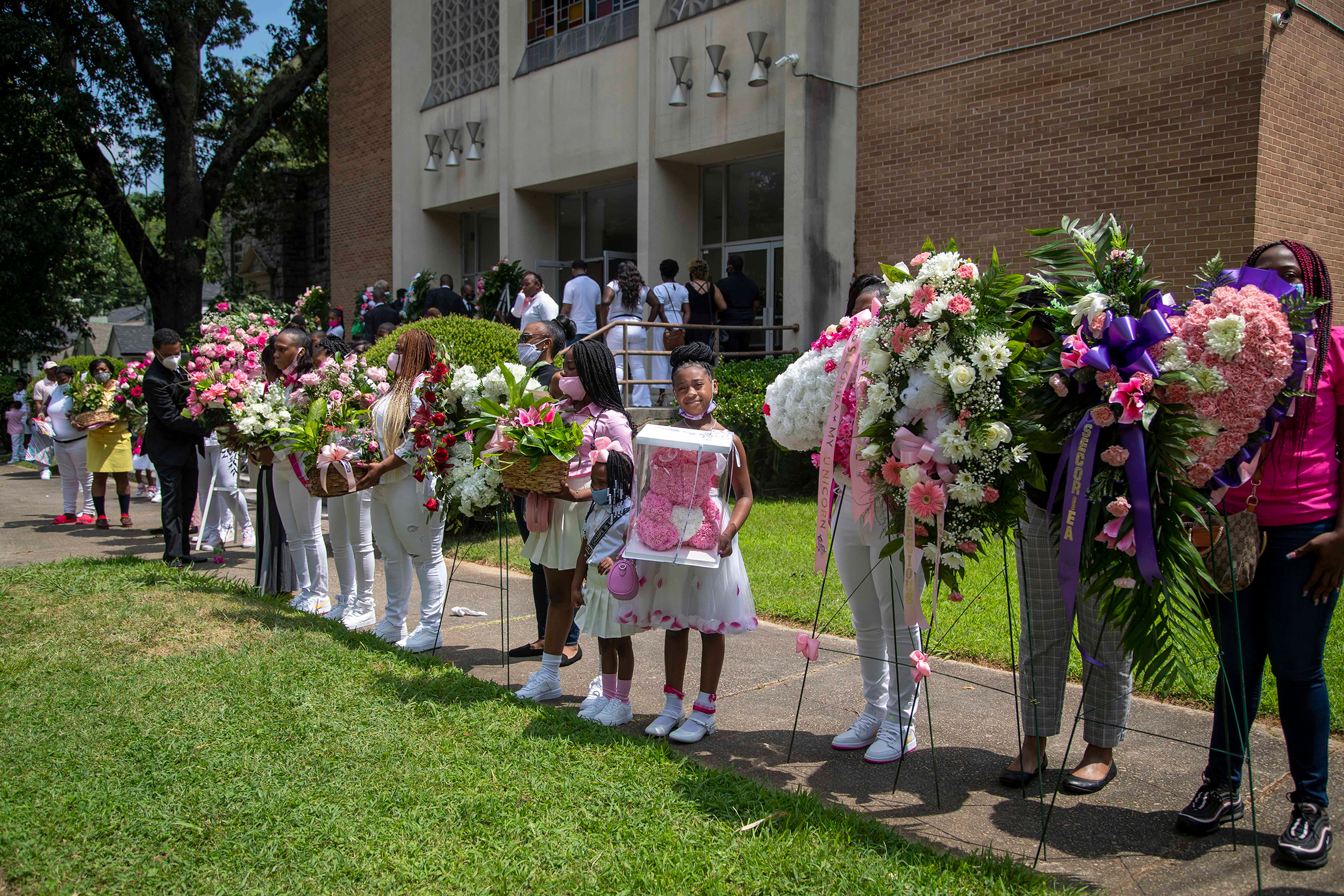 Family and friends of Secoriea Turner, an eight-year-old who was fatally shot while in a car with her mother near the site where Rayshard Brooks was killed by a police officer weeks earlier, leading to protests against police brutality, present floral arrangements during her home-going service at New Calvary Missionary Baptist Church in Atlanta on July 15.