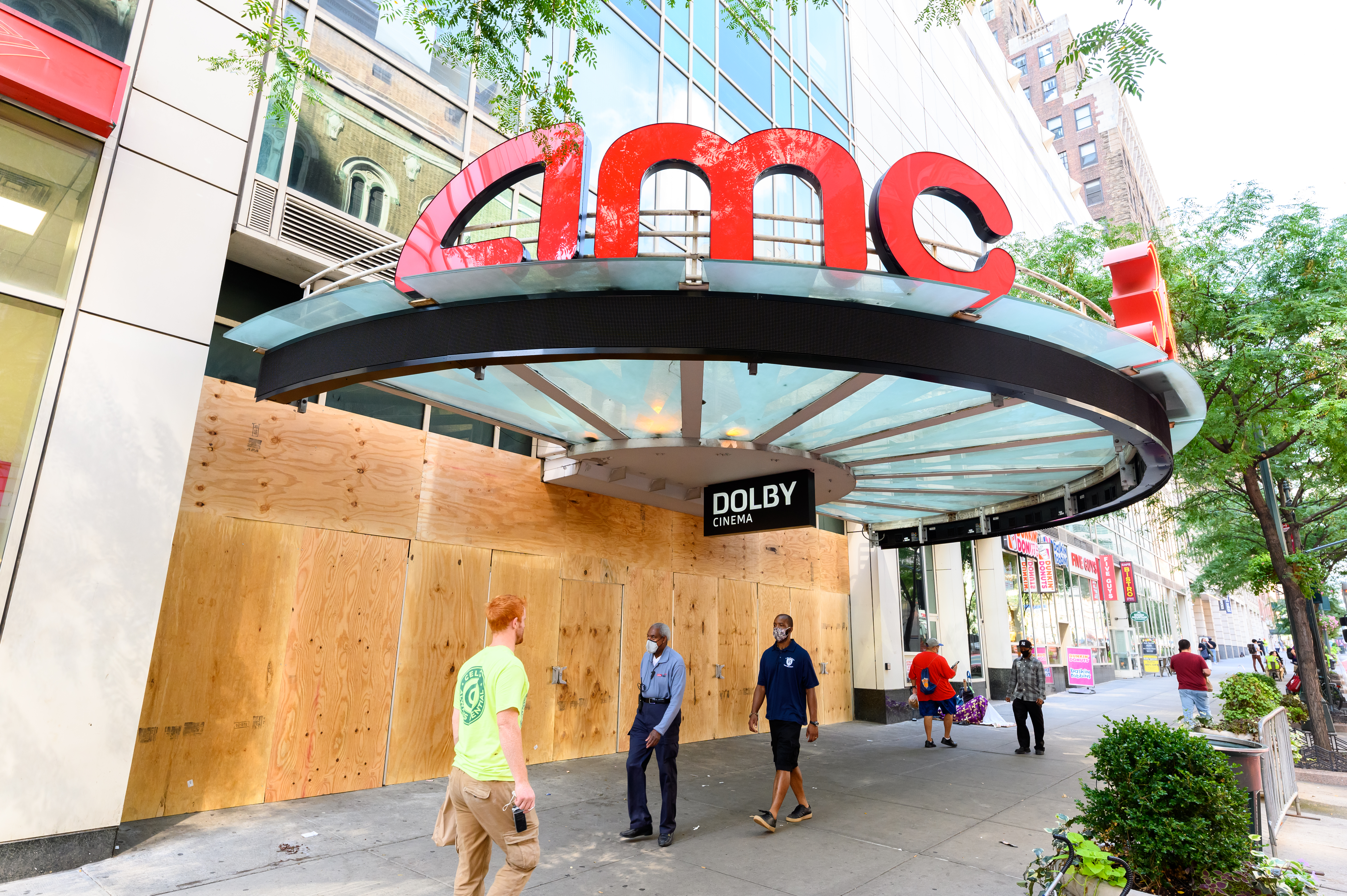 People walk outside the newly boarded AMC 34th Street 14 movie theater