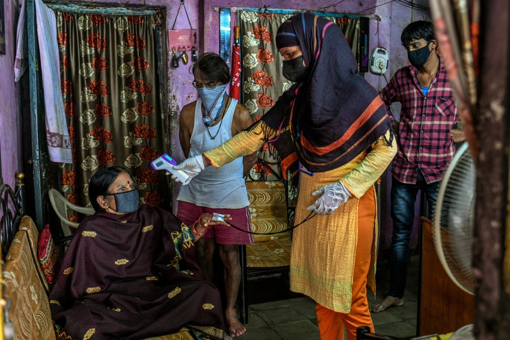 A health care worker checks a woman's temperature and oxygen saturation in the Dhole Patil slum of Pune, India, on Aug. 10.
