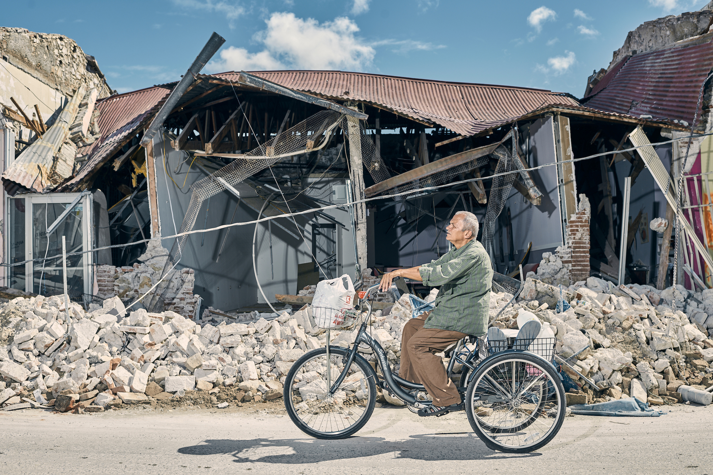 A man rides his tricycle in front of earthquake-destroyed buildings in the town center of Guanica, Puerto Rico, on Jan. 8.