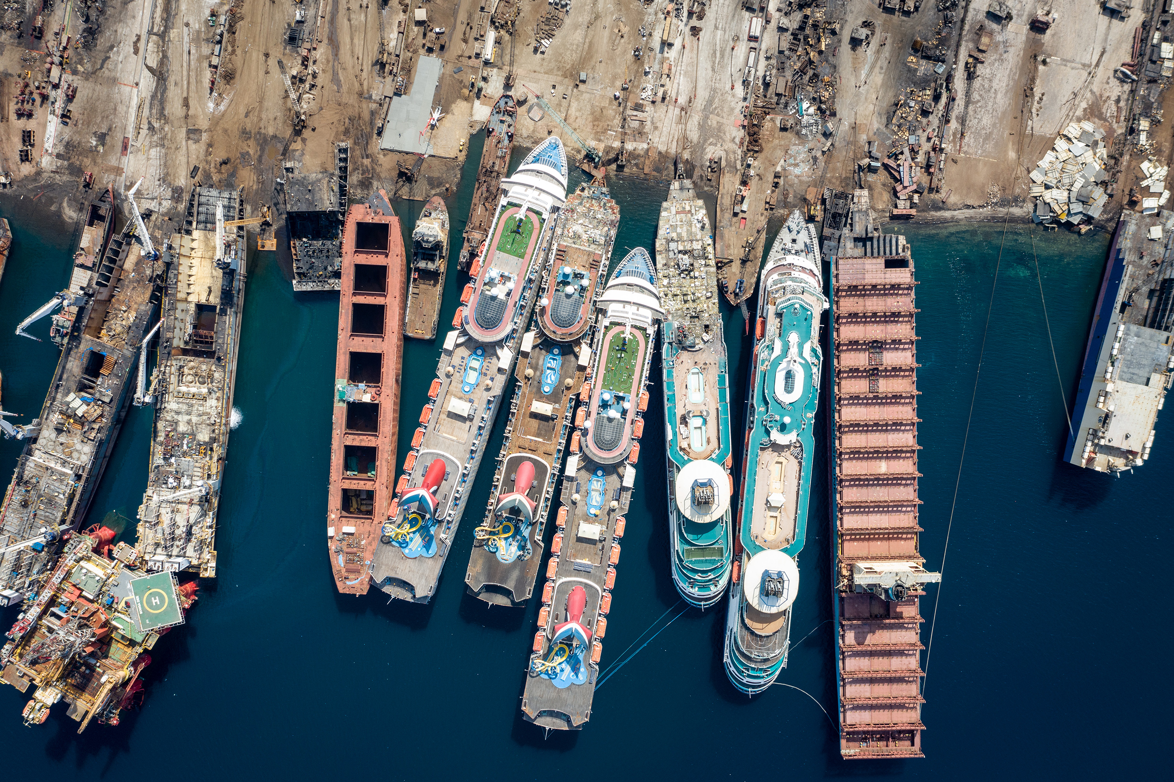 Five luxury cruise ships are seen while being broken down for scrap metal at the Aliaga ship recycling port in Izmir, Turkey, on Oct. 2. As the global pandemic slowed the multi-billion dollar cruise industry, and with public confidence in cruise vacations down after a series of outbreaks, some operators have been forced to cut losses and retire ships earlier than planned. The crisis, however, has bolstered the year's intake of ships at this port.